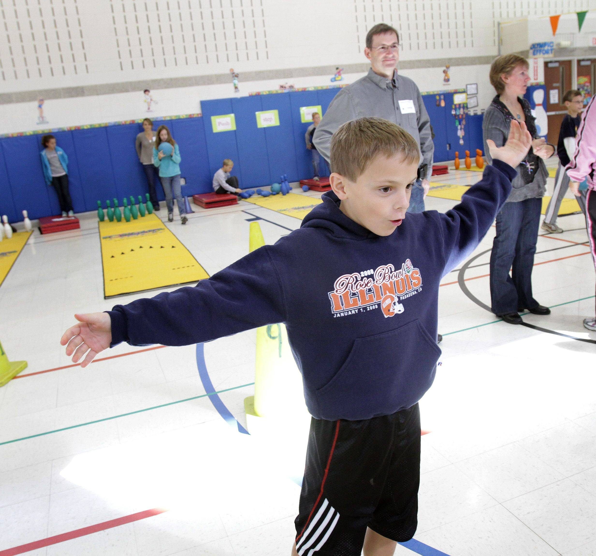 Fifth-grader Joseph Gaither reacts as the pins go down as his dad, Joseph Sr., look on.