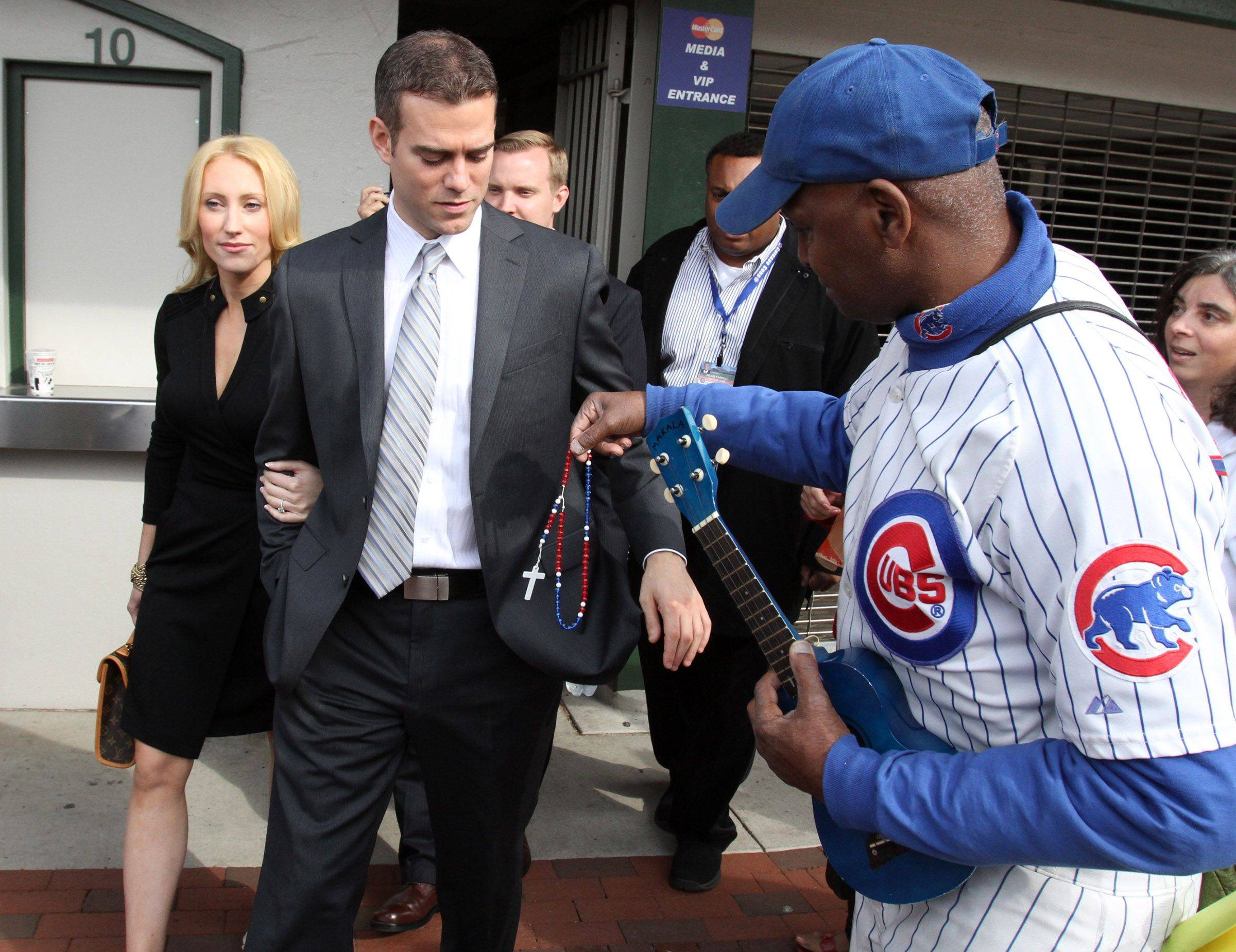 "Ronnie ""Woo Woo"" Wickers hands Theo Epstein, Chicago Cubs president of baseball operations, rosary beads as Epstein was touring Wrigley Field with his wife Marie in Chicago on Tuesday."