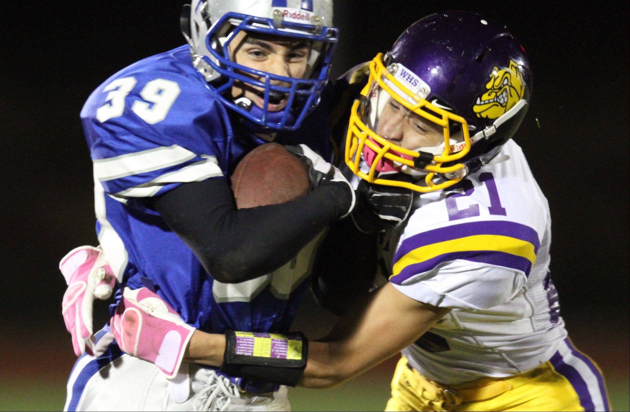 Vernon Hills' Sam Maloof is pulled down by Wauconda's Chris Bednarski at Vernon Hills on Friday.