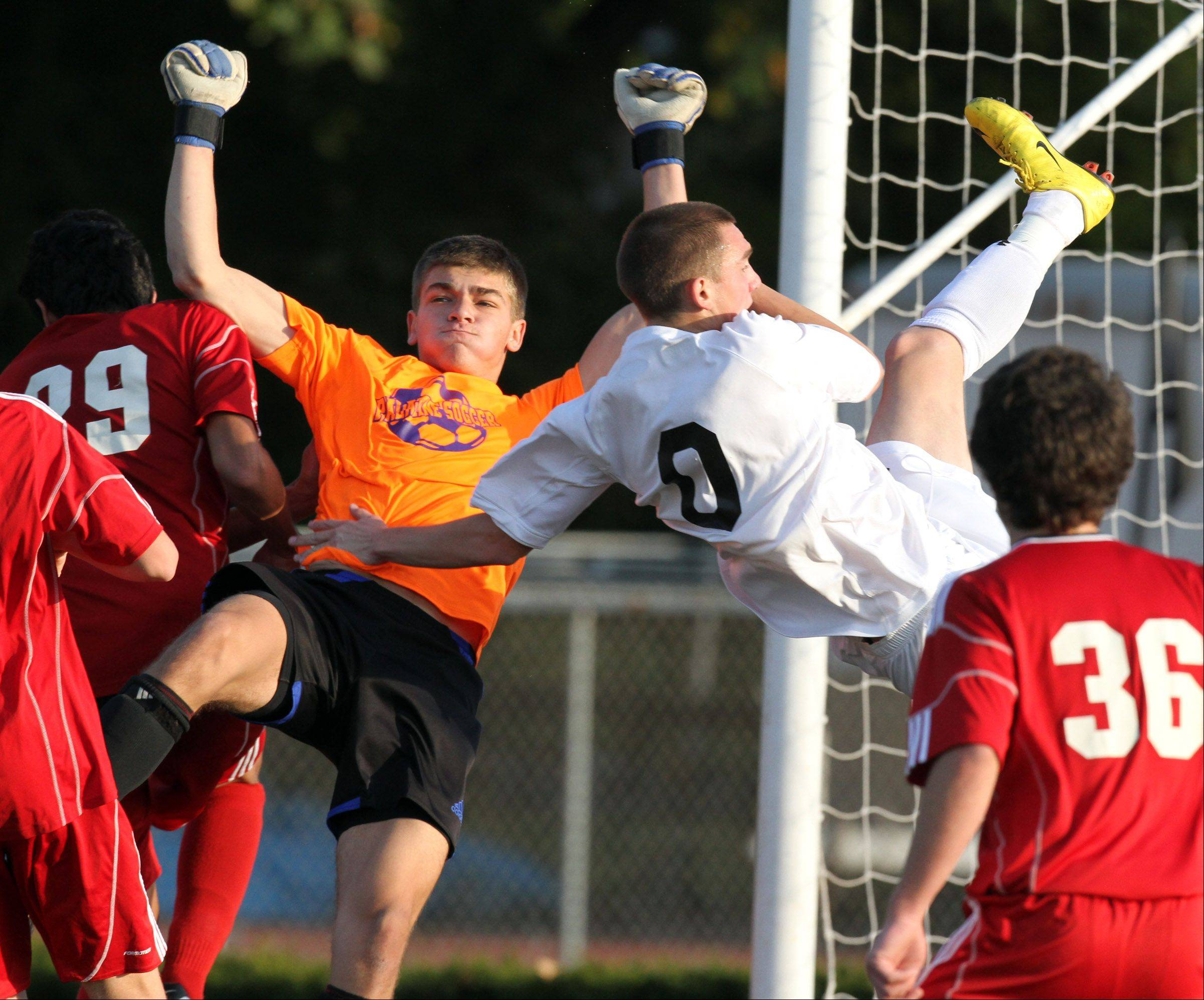 Libertyville's Austin Bitta crashes into Palatine goalkeeper Evan Held Saturday in Libertyville.