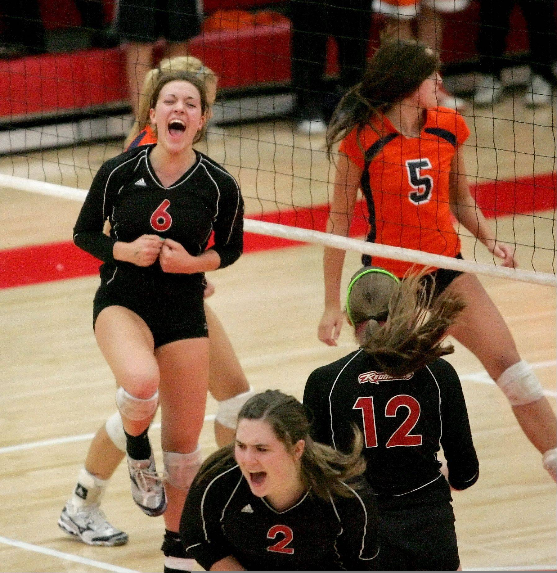 Naperville Central's Alysia Baznik, left, celebrates a point with teammates during Tuesday's volleyball match against Naperville North.