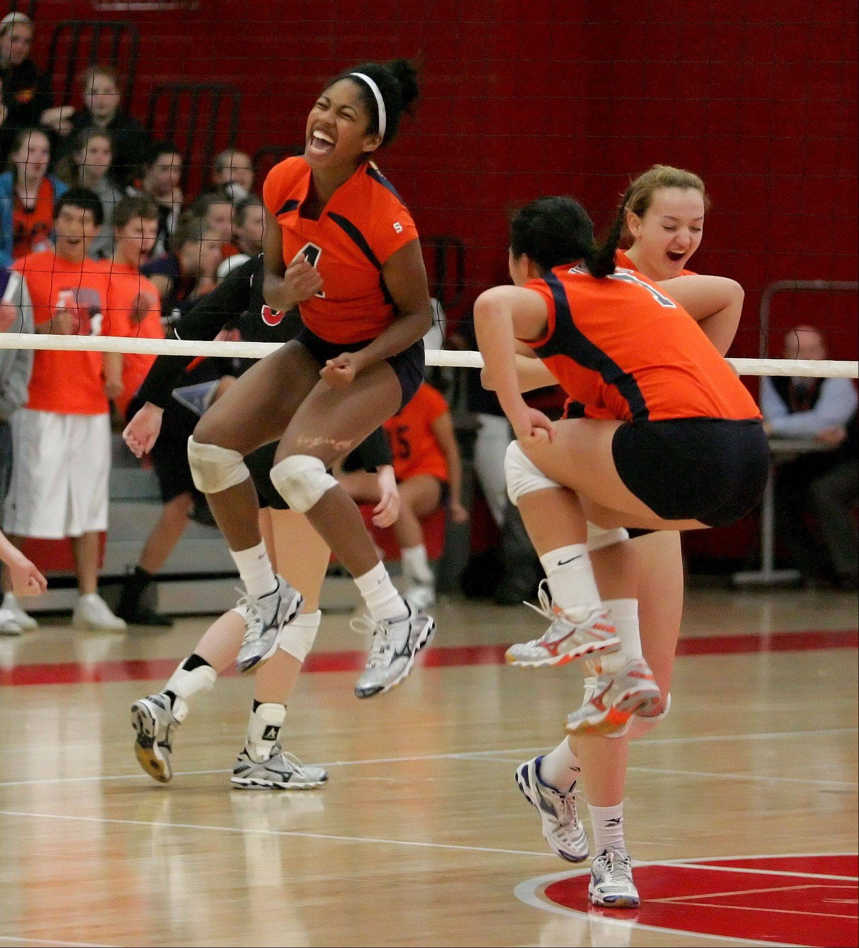Naperville North's Ashley Crawford, left, and teammates celebrate a point won over Naperville Central in girls volleyball action on Tuesday.