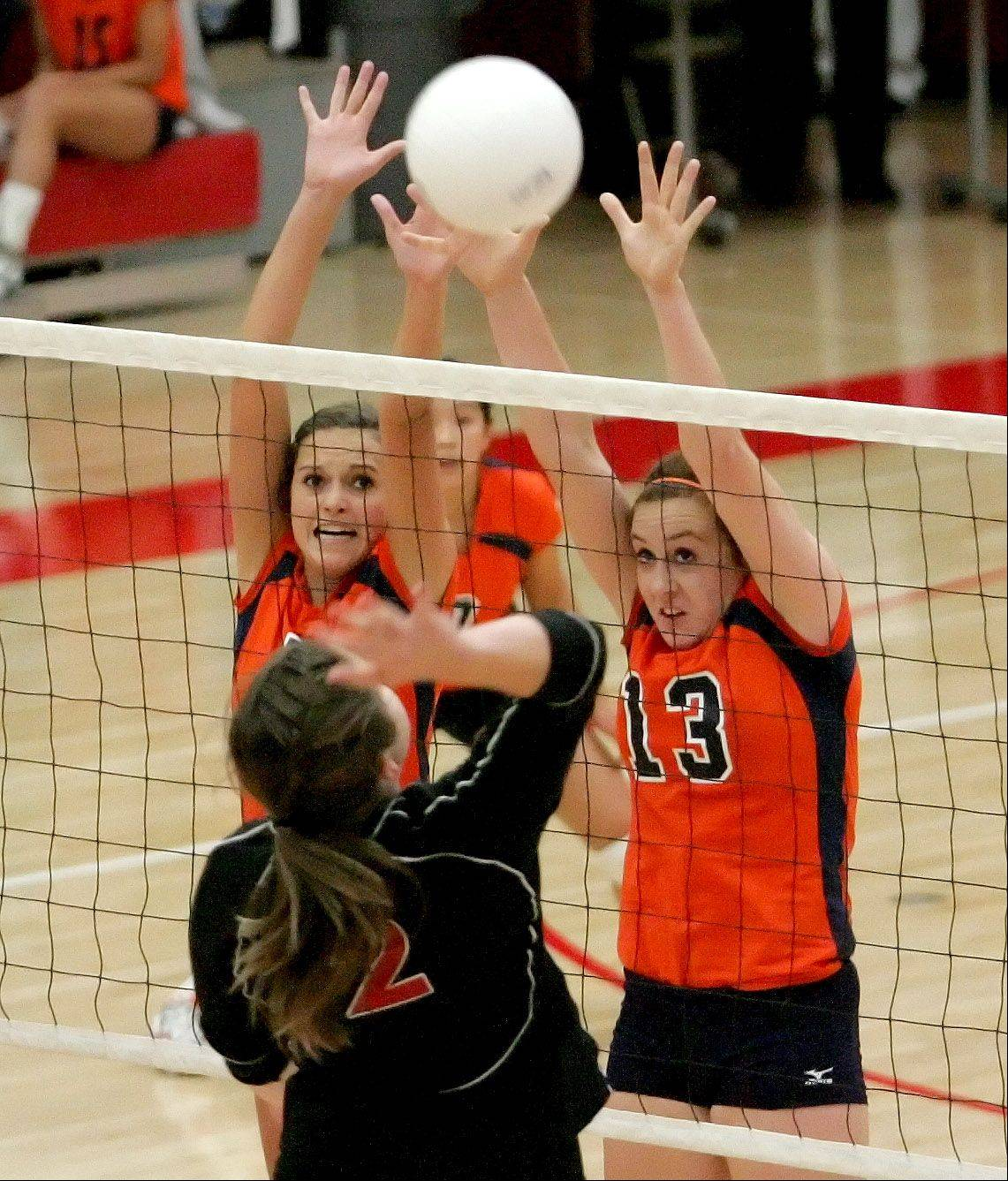 Bailey O'Drobinak, left and Corinne Gajcak, right, of Naperville North reach to block a shot in action against Naperville Central on Tuesday.