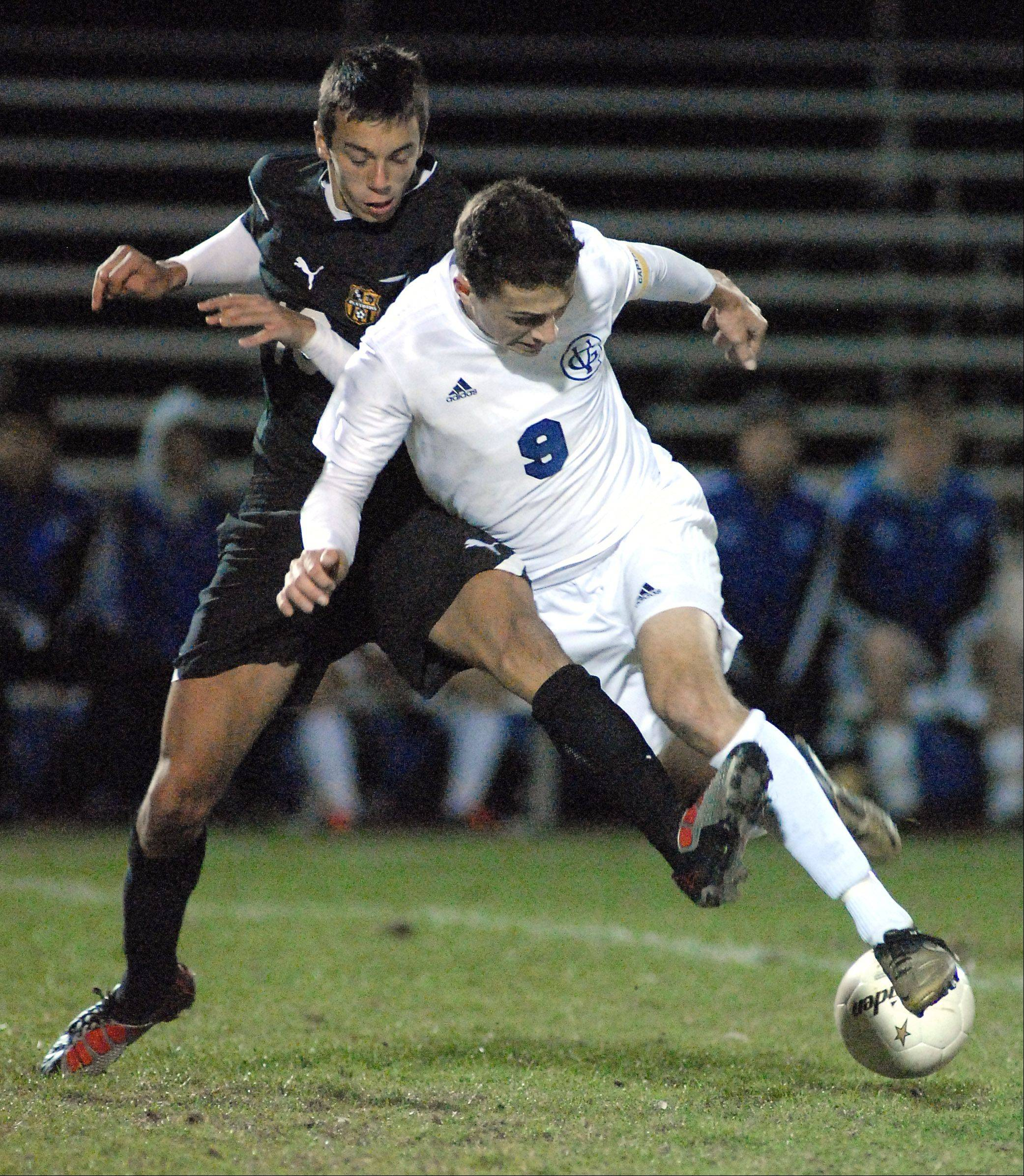 Geneva's Kevin Higgins goes down while battling for the ball against Glenbard North's Kevin Noval during Tuesday's regional soccer game at Elk Grove High School.