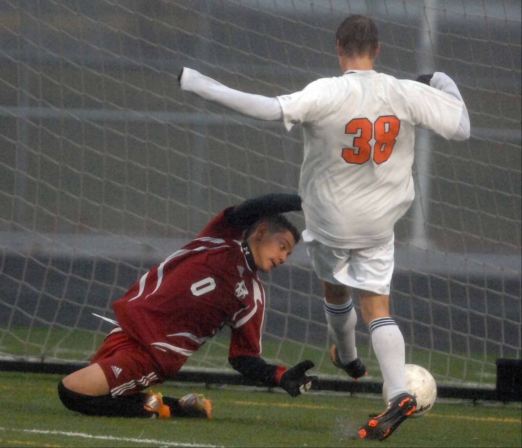 Naperville North's Evan Trychta drills one into the goal against Oswego Wednesday.