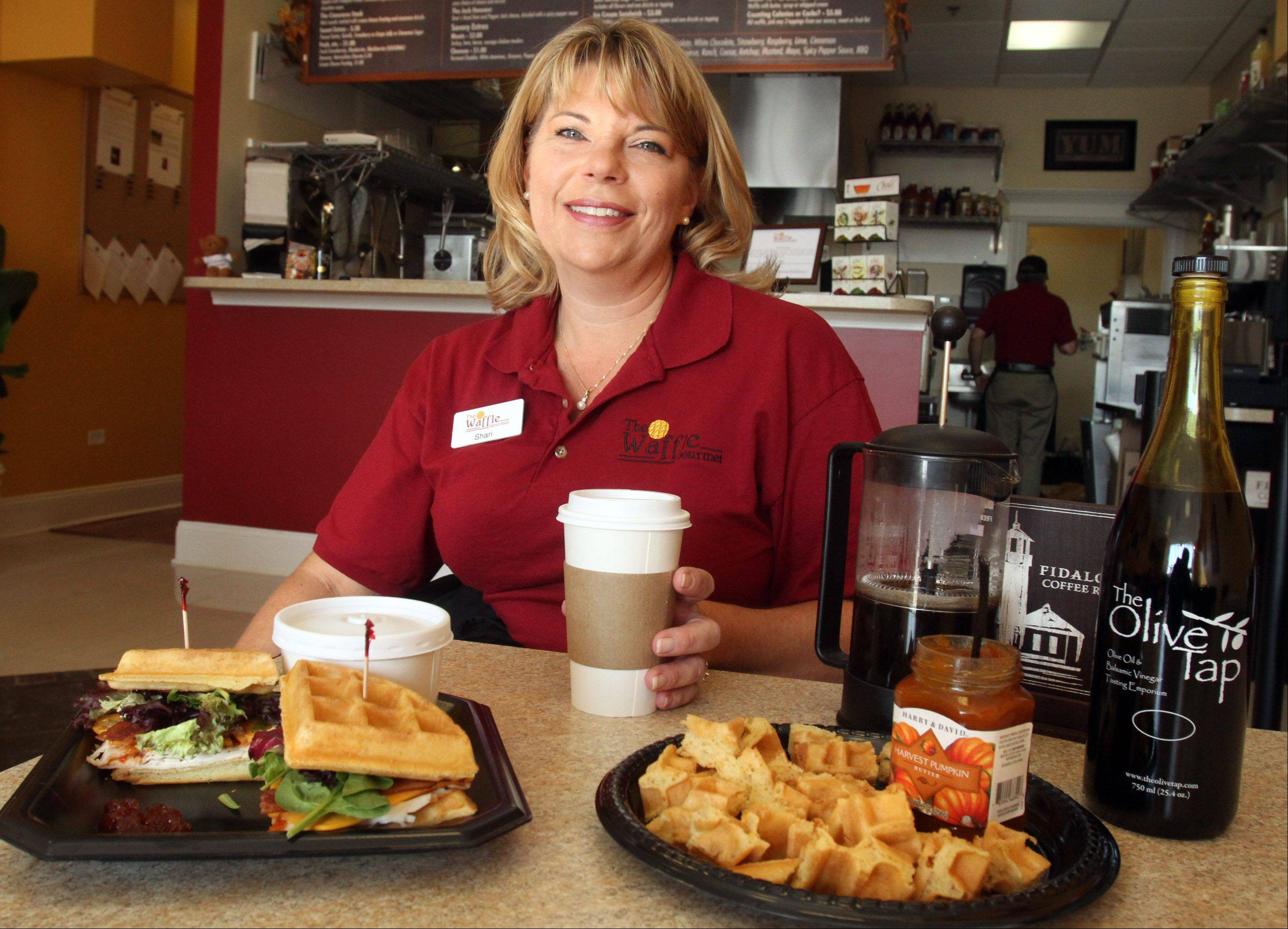 Shari Sorrells, owner of The Waffle Gourmet at Deer Park Town Center, serves an array of sandwiches including the waffle turkey, bacon and cheddar sandwich and a sample that she keeps at the counter.