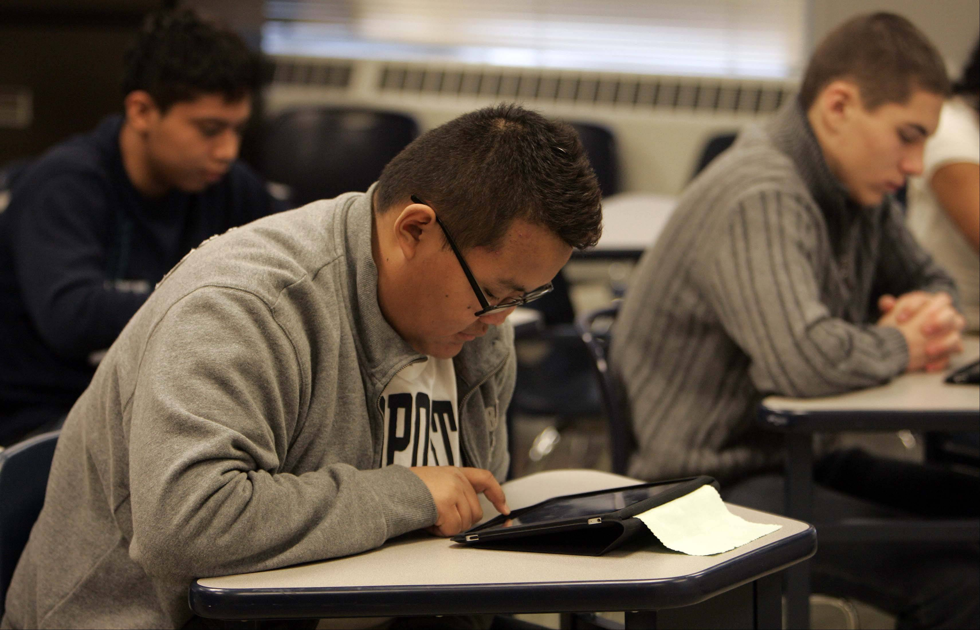 Bayar Enkhtuvshin, 16, studies on his iPad during class at the Northwest Suburban High School District 214 Newcomer Center in Arlington Heights. District 214 is running 20 tablet computer pilot programs in its schools this year to test their uses in the classroom. They hope that with