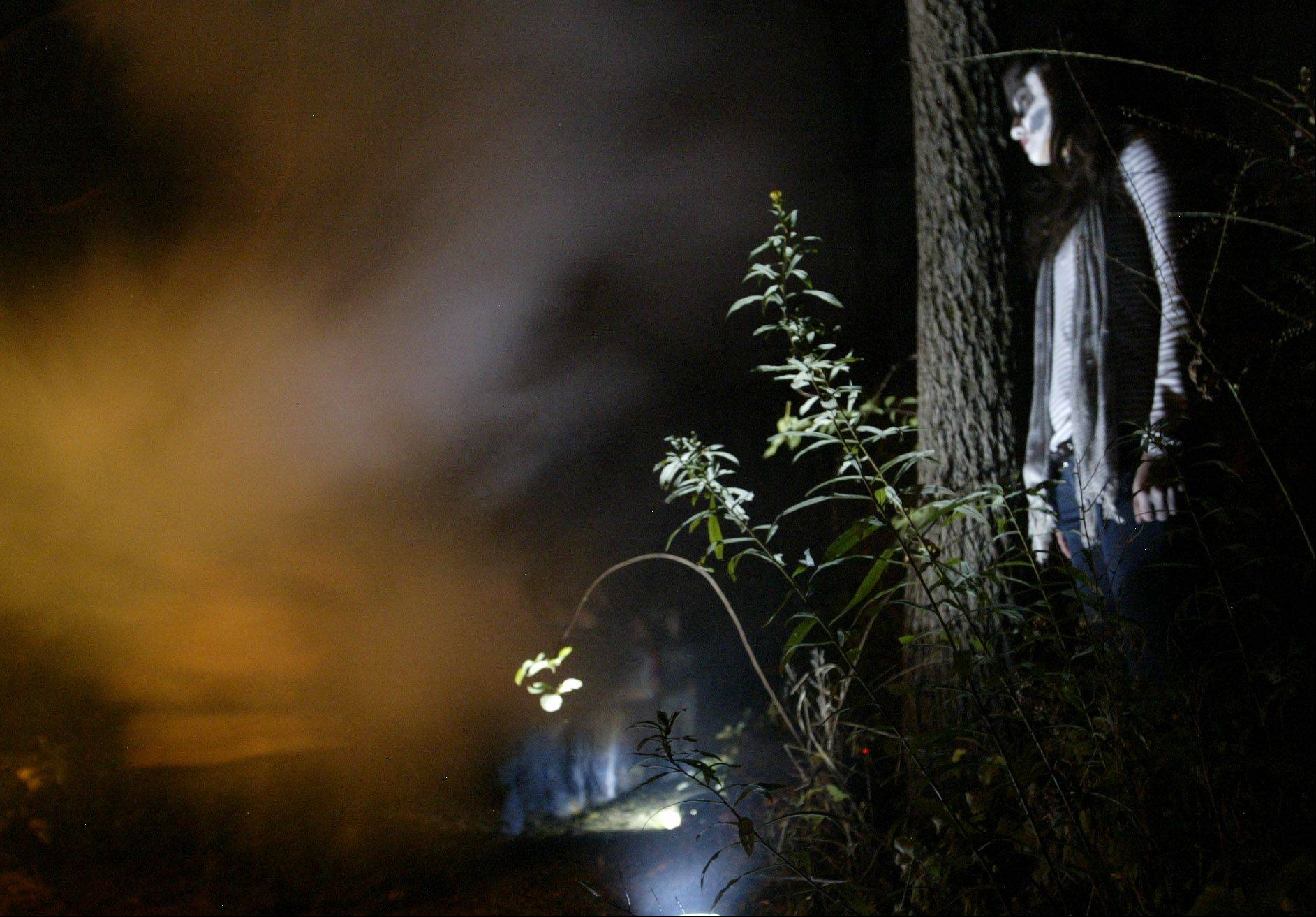Amanda Rodriguez, 17, of Aurora, waits to scare guests during a haunted hike Friday in Elgin.