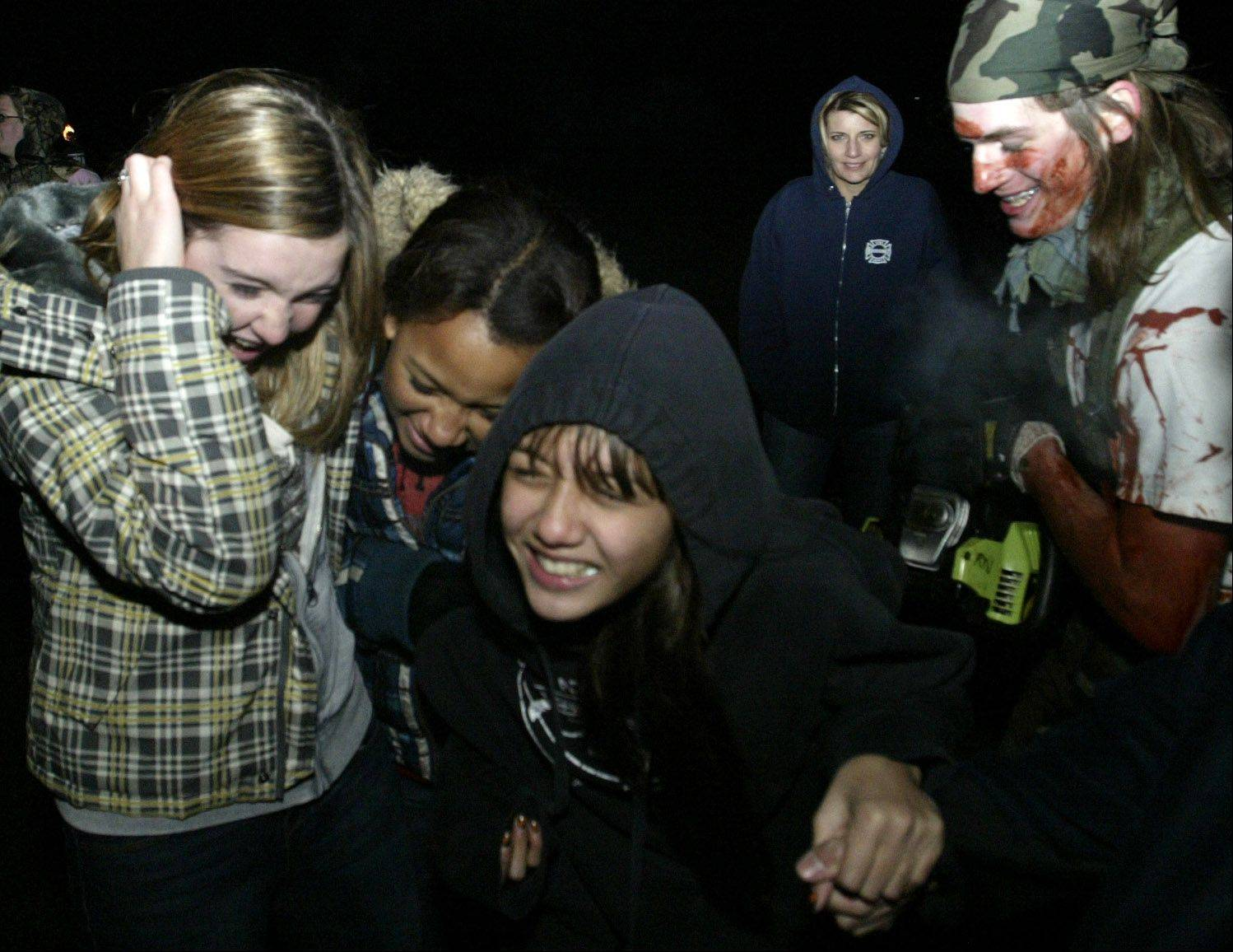 Jesse Rohloff, 19, of Elgin scares, from left, Michele Ruiz, 13, of Gilberts; Kaycee Cooper, 13, of Gilberts; and Amanda Groves, 13, of Algonquin during the Burden Acres Haunted Hike at Camp Big Timber in Elgin.