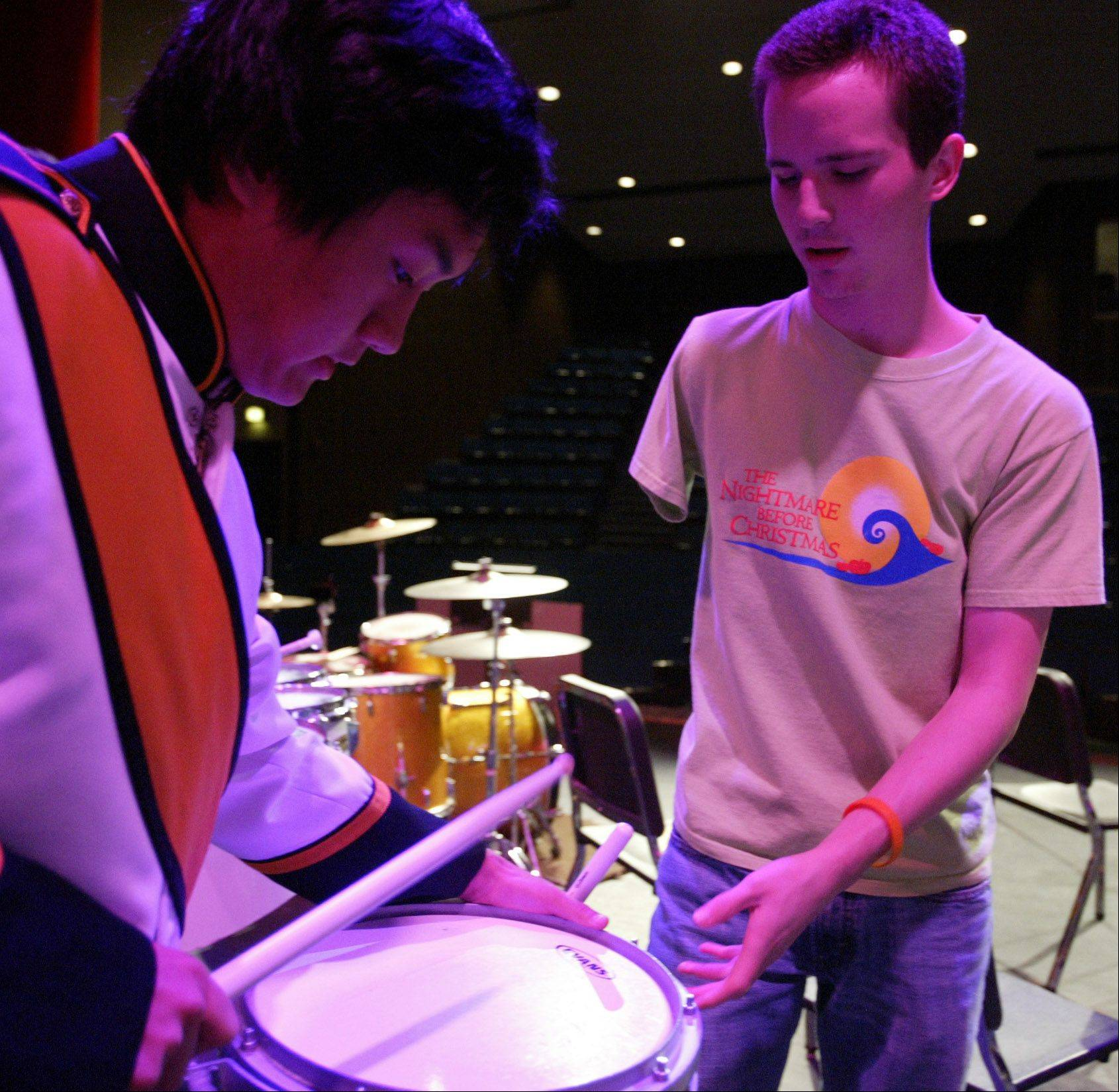 Justin Miller, 19, of Streamwood, helps the Streamwood High School drum line warm up before their school concert Oct. 20. Miller, who has played drums since he was little, lost his dominant arm to cancer.