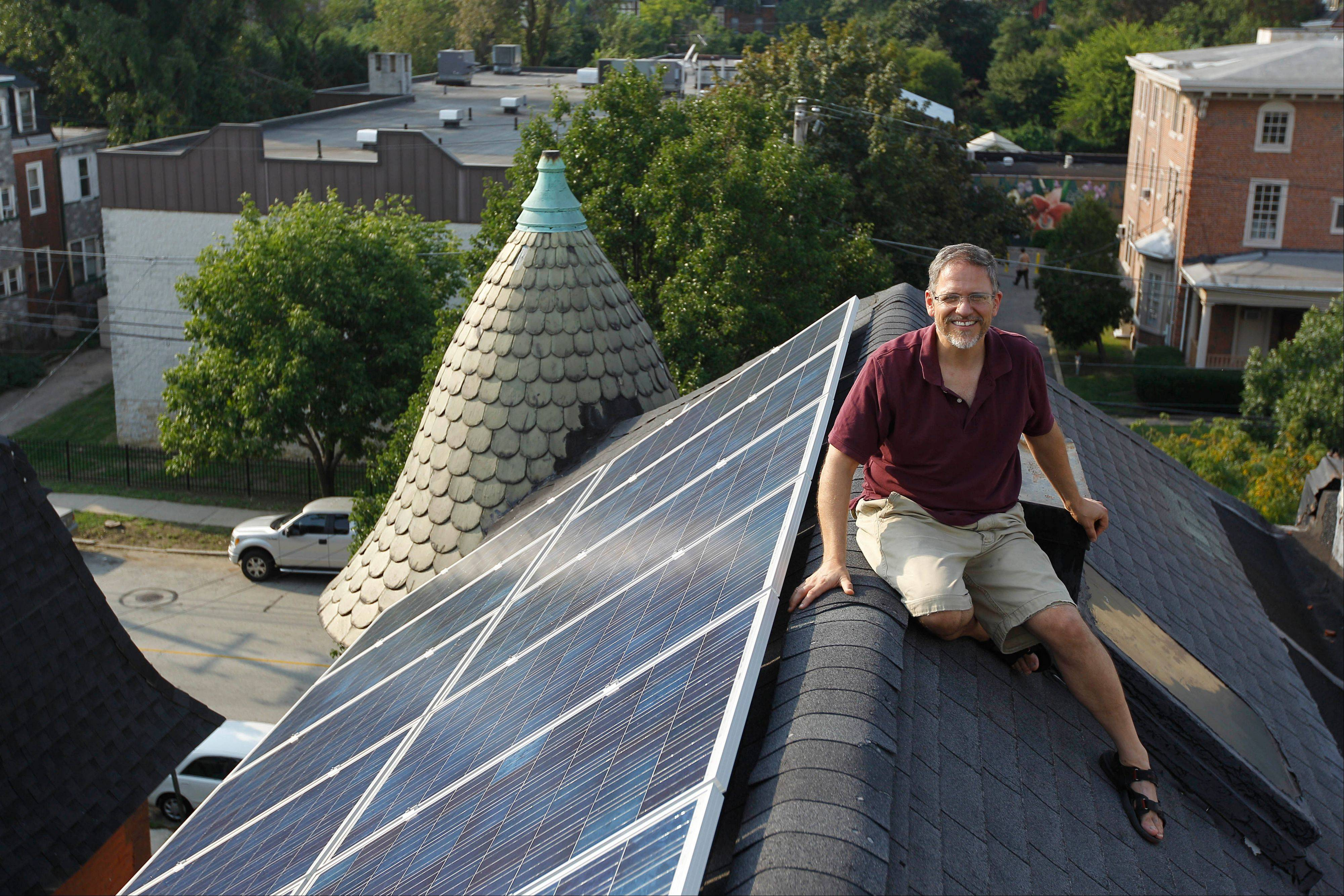 Tim Johnson poses for a portrait with solar panels on his roof in Philadelphia. Since March, he has generated 50 percent to 75 percent of his electricity with a set of solar panels on his roof, saving 20 percent on his electricity bills.
