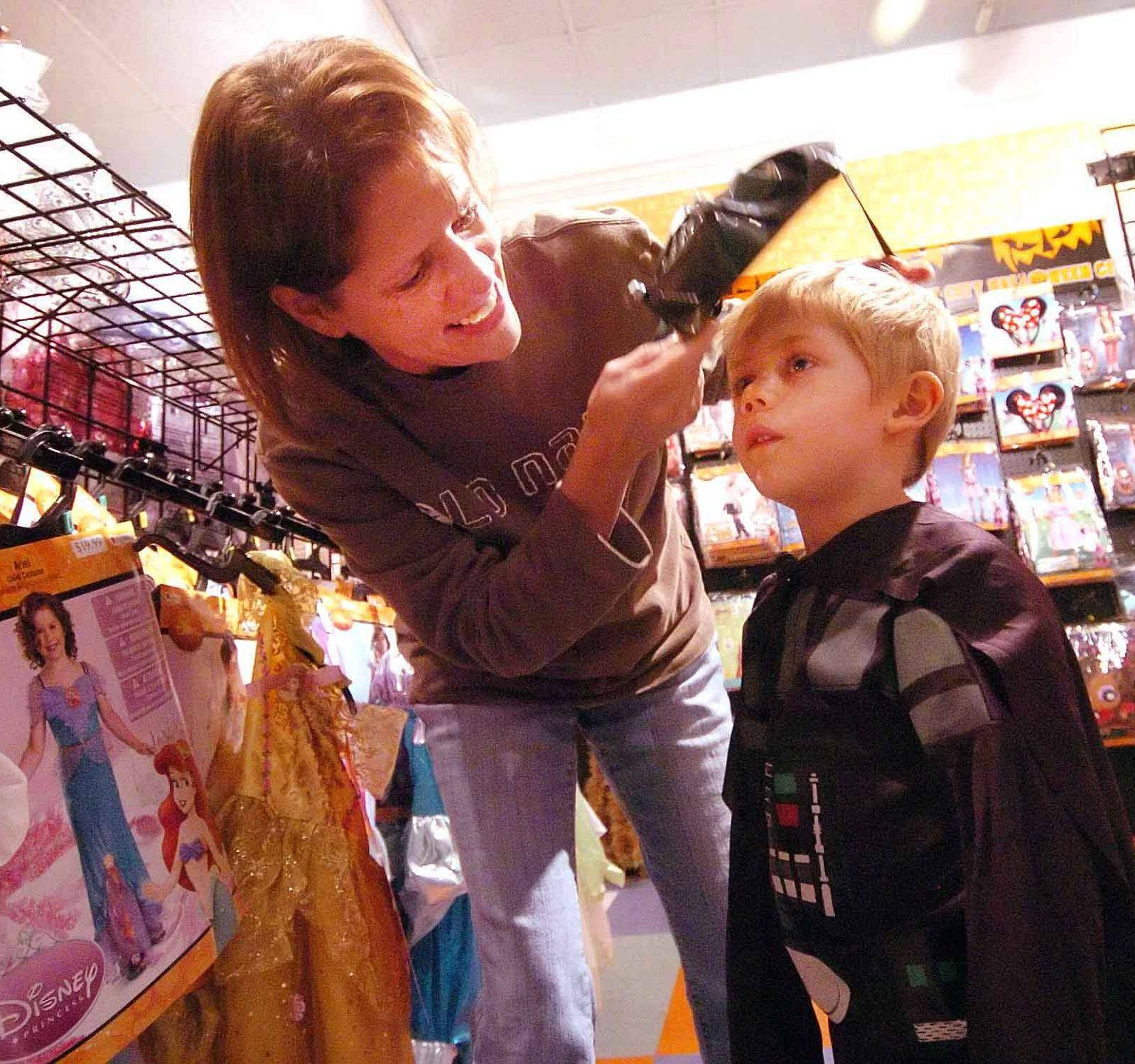 Mary Reetz helps her son Max with his Darth Vader costume Thursday at Halloween City in Downers Grove.