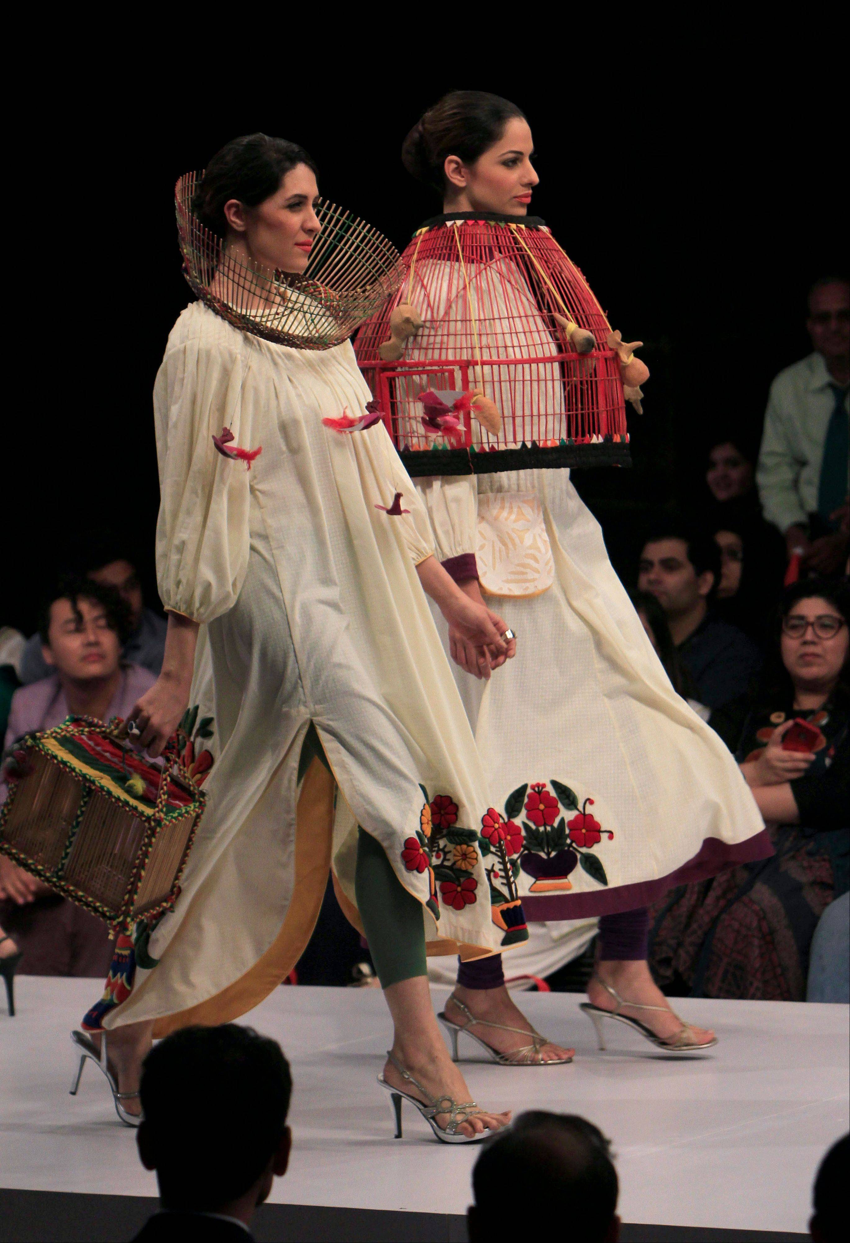 Models present creations of a Pakistani designer M Irfan Ali during a fashion show in Karachi, Pakistan on Friday, Oct. 21, 2011.