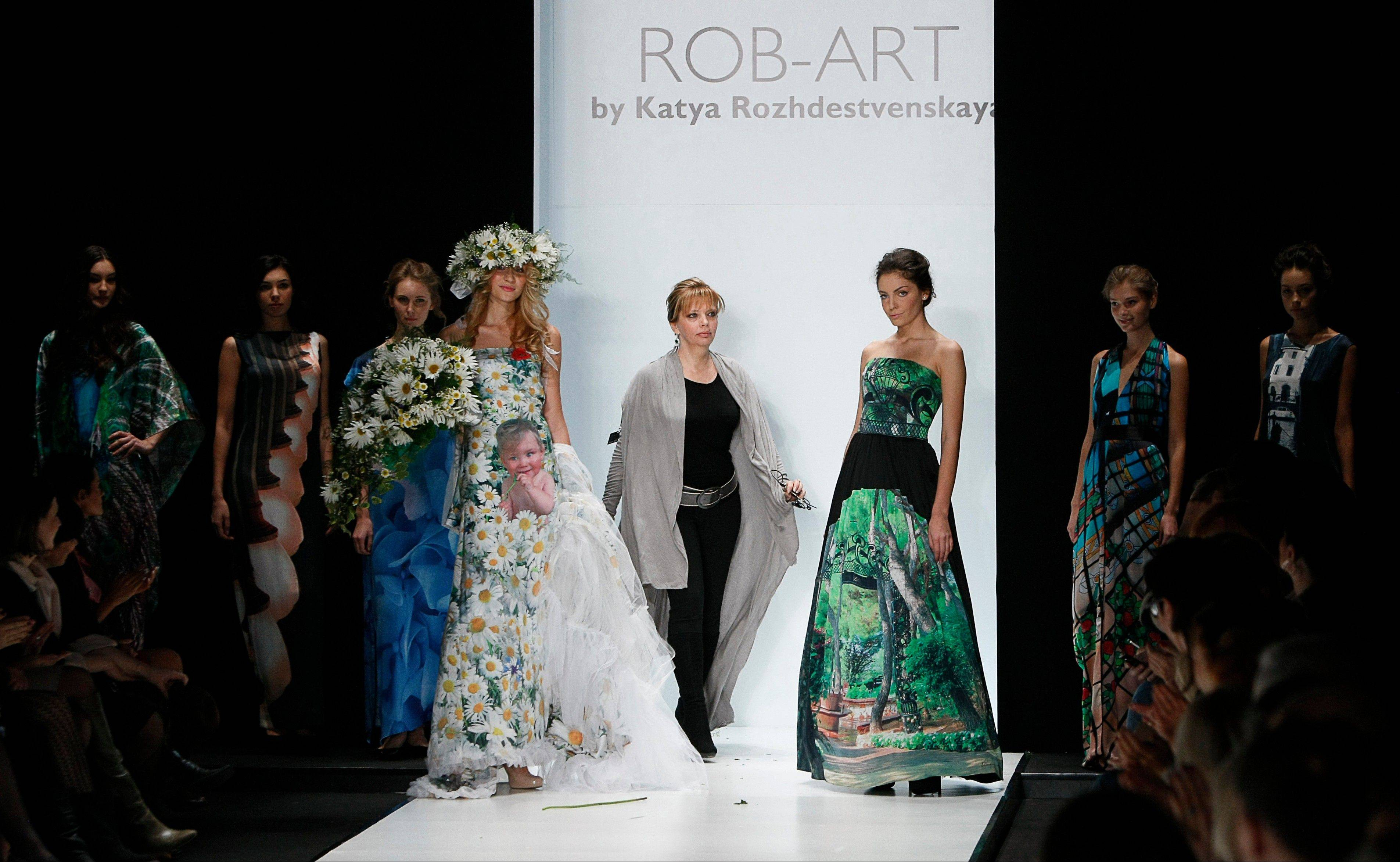 Models dressed in ROB-ART creation greet Russian designer Katya Rozhdestvenskaya, center, during Spring-Summer 2012 collection at Mercedes-Benz Fashion Week in Moscow, Russia, Tuesday, Oct. 25, 2011.