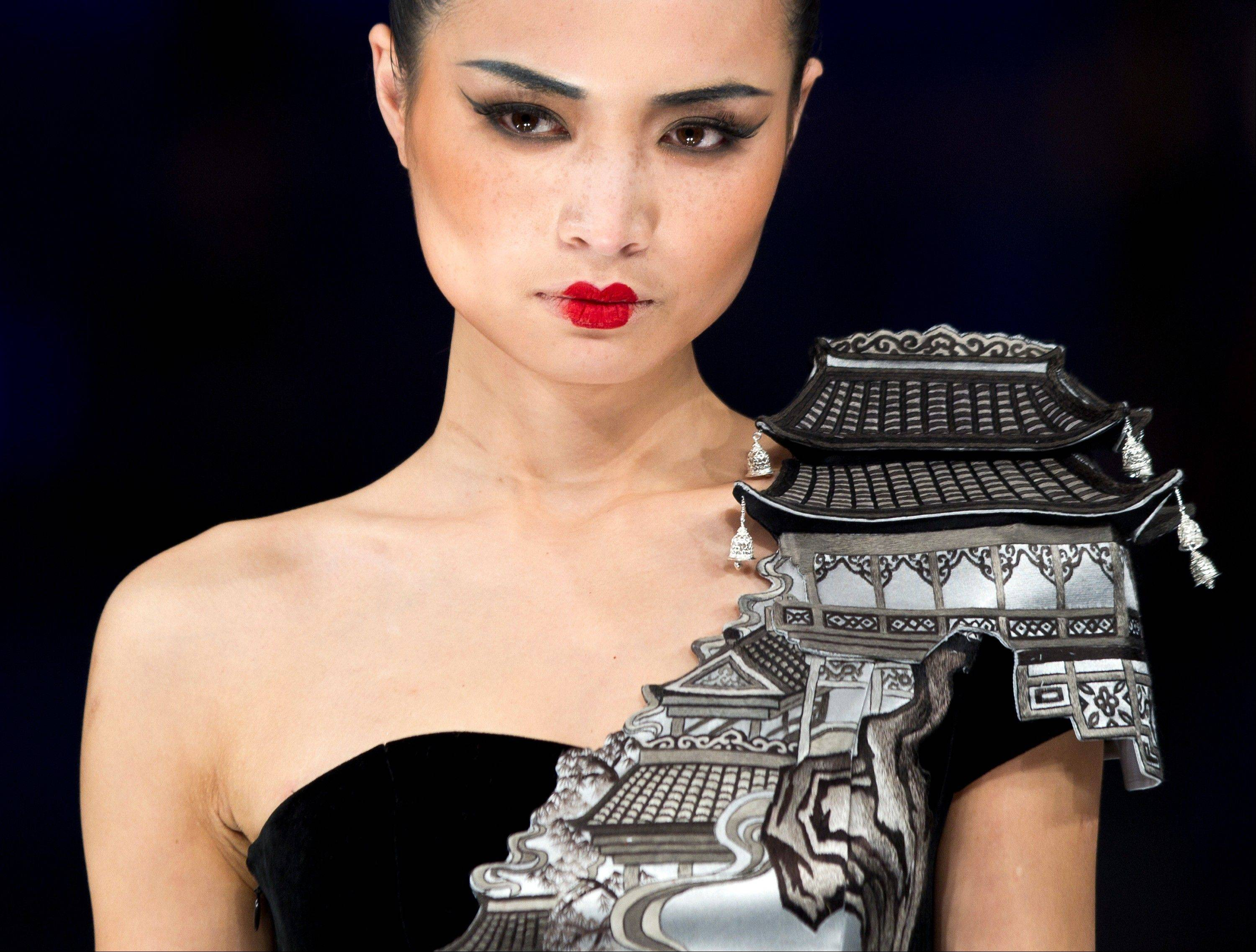 "A model displays a creation by NE TIGER Couture 2012 collection with the theme ""Tang Dynasty"" during China Fashion Week for Spring/Summer 2012 in Beijing, China, Tuesday, Oct. 25, 2011."