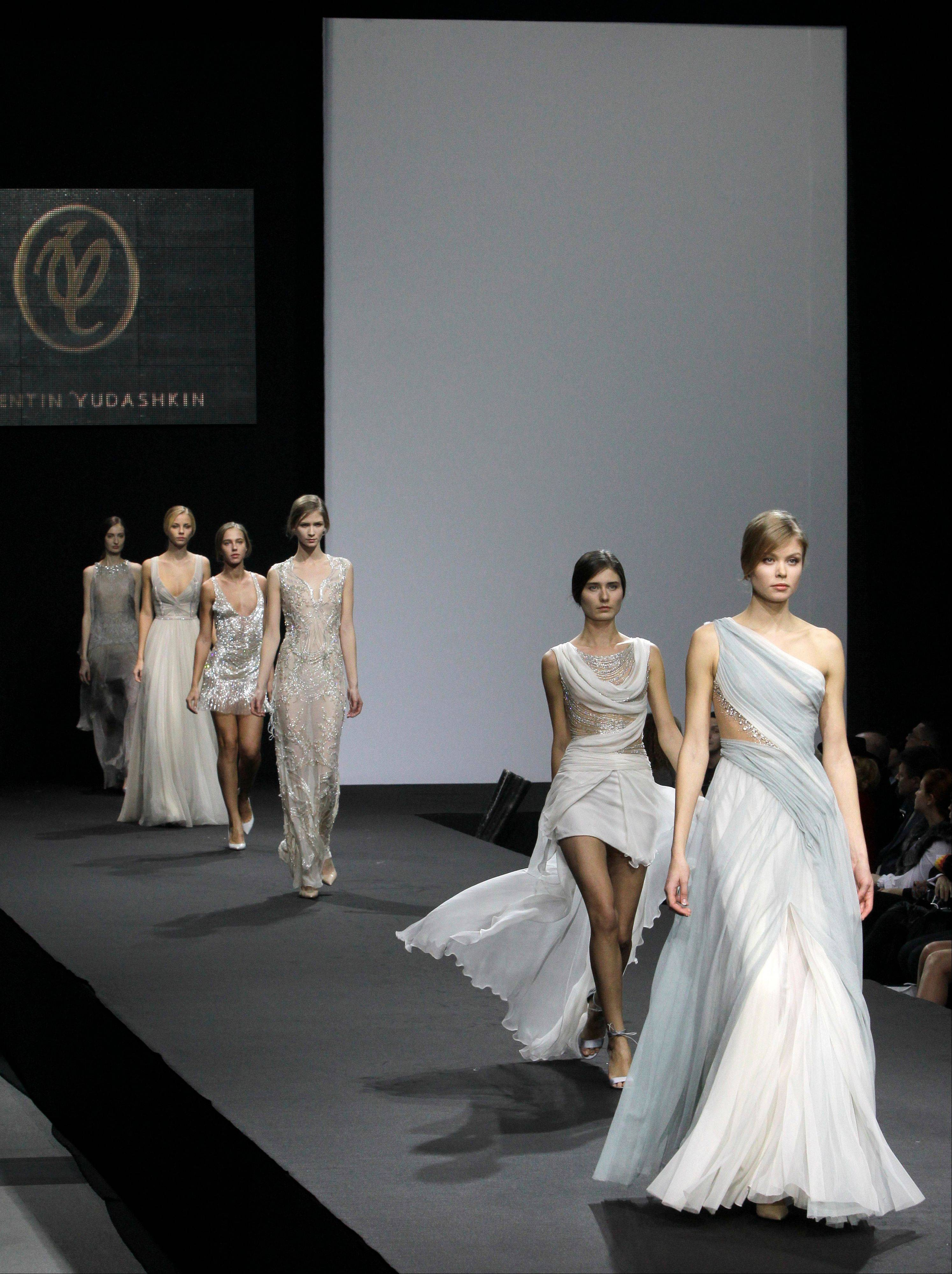 Models display creations by Russian designer Valentin Yudashkin during the Volvo Fashion Week in Moscow, Russia, Wednesday, Oct. 26, 2011.