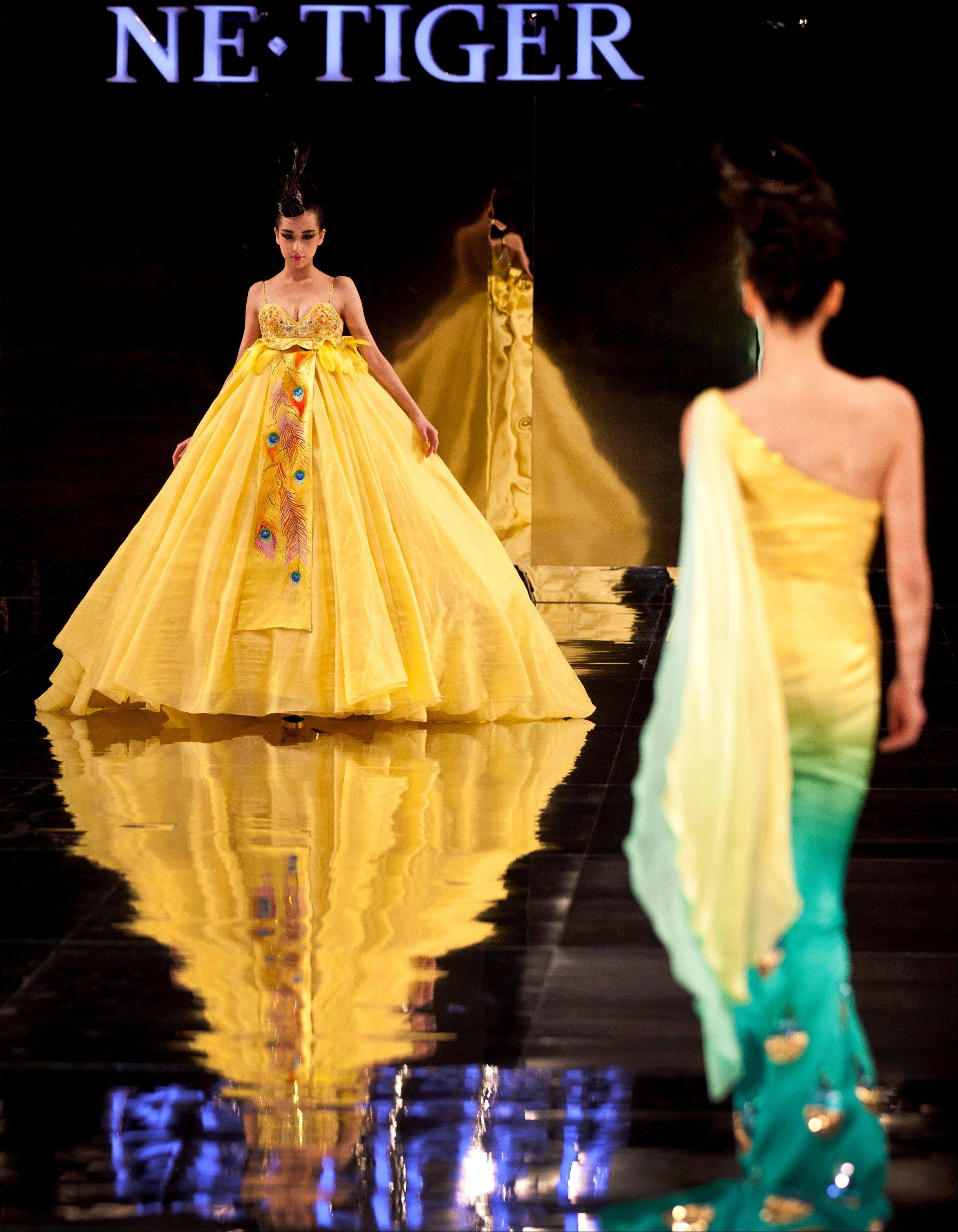"Models present creations by NE TIGER Couture 2012 collection with the theme ""Tang Dynasty"" during China Fashion Week for Spring/Summer 2012 in Beijing, China, Tuesday, Oct. 25, 2011."
