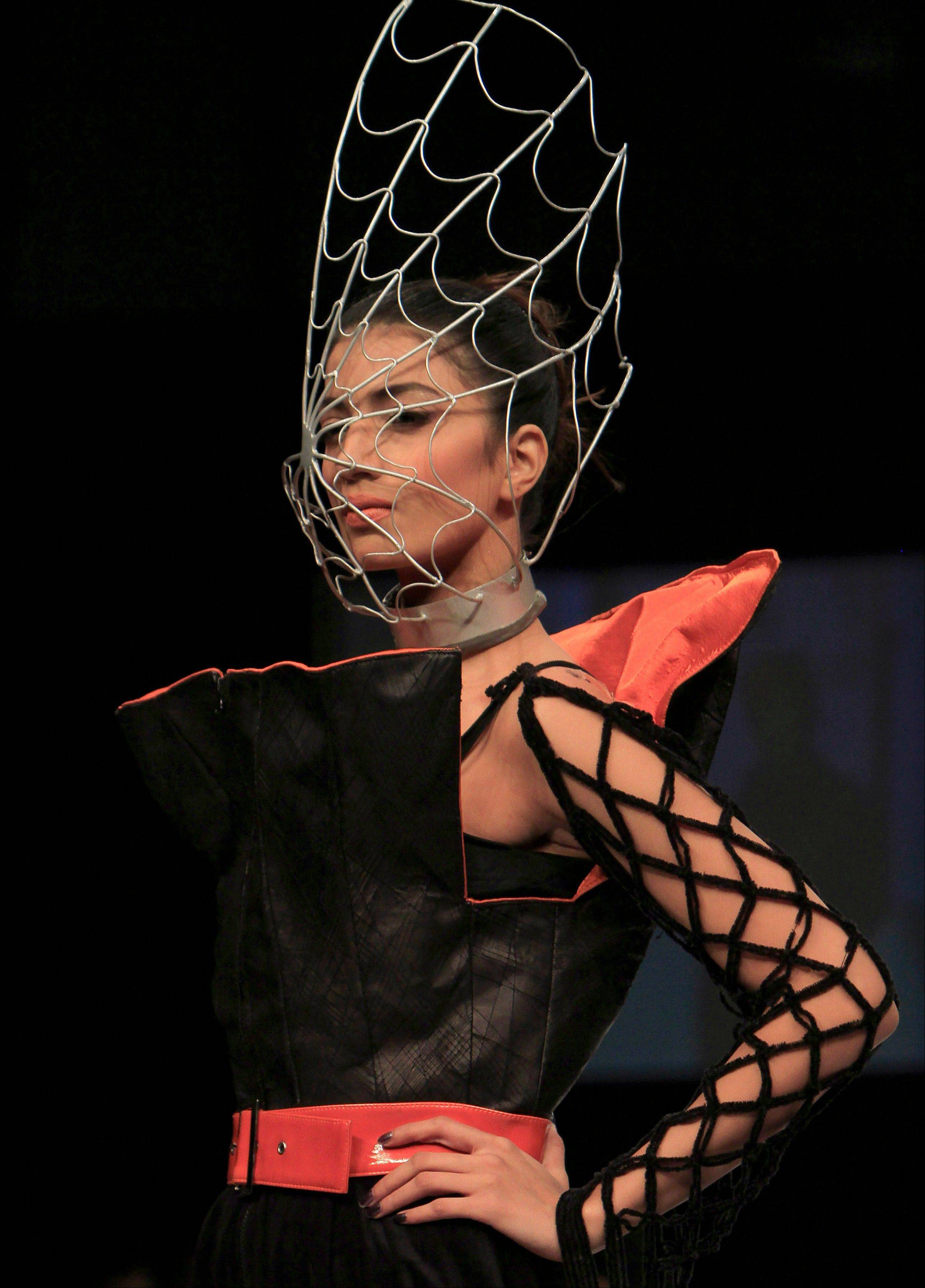 A model displays a creation by Pakistani designer Zaheer Abbas during a Fashion show in Karachi, Pakistan on Thursday, Oct. 20, 2011.