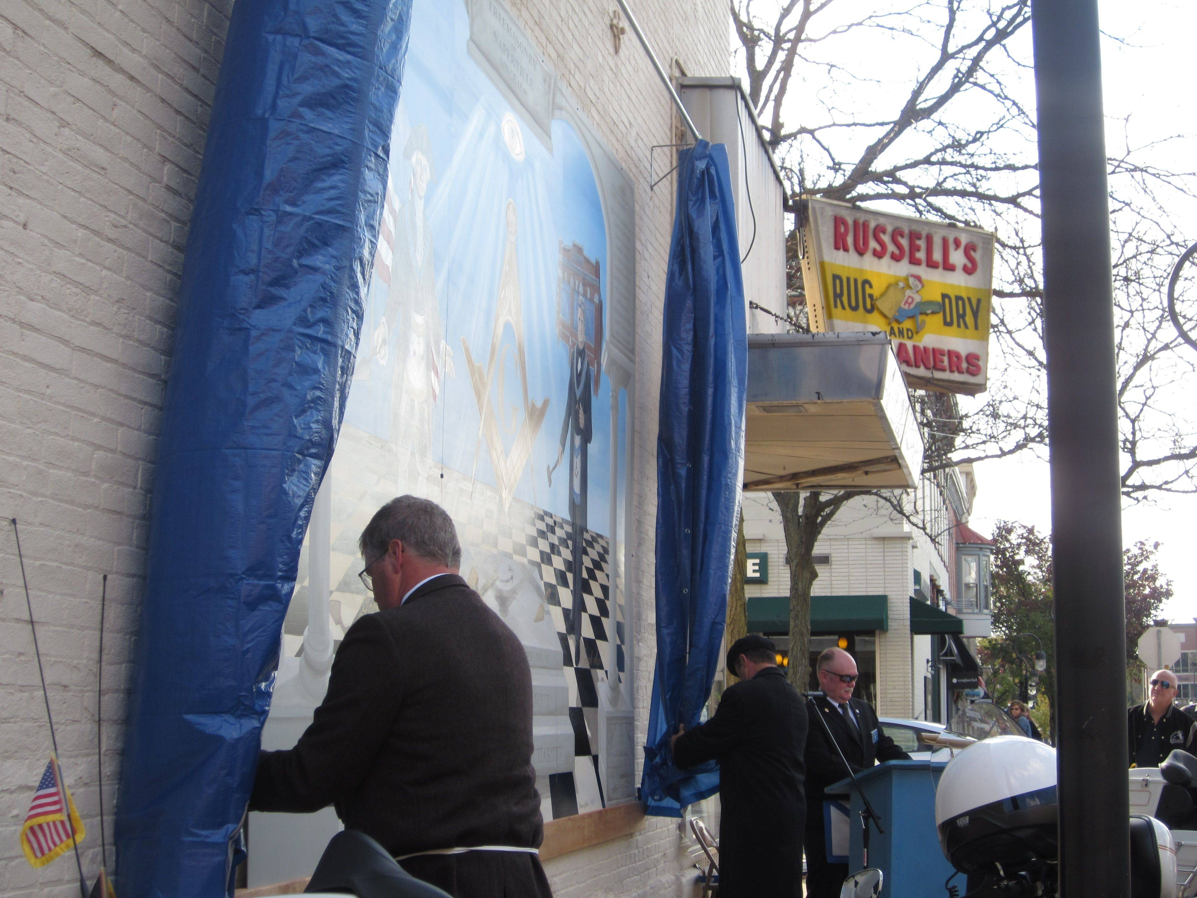 "Naperville Century Walk's 40th piece of art, ""Faith, Hope and Charity"" by Marianne Lisson-Kuhn, is unveiled Saturday morning. The mural depicting the values of freemasonry was sponsored by Euclid Lodge 65 and the Century Walk."