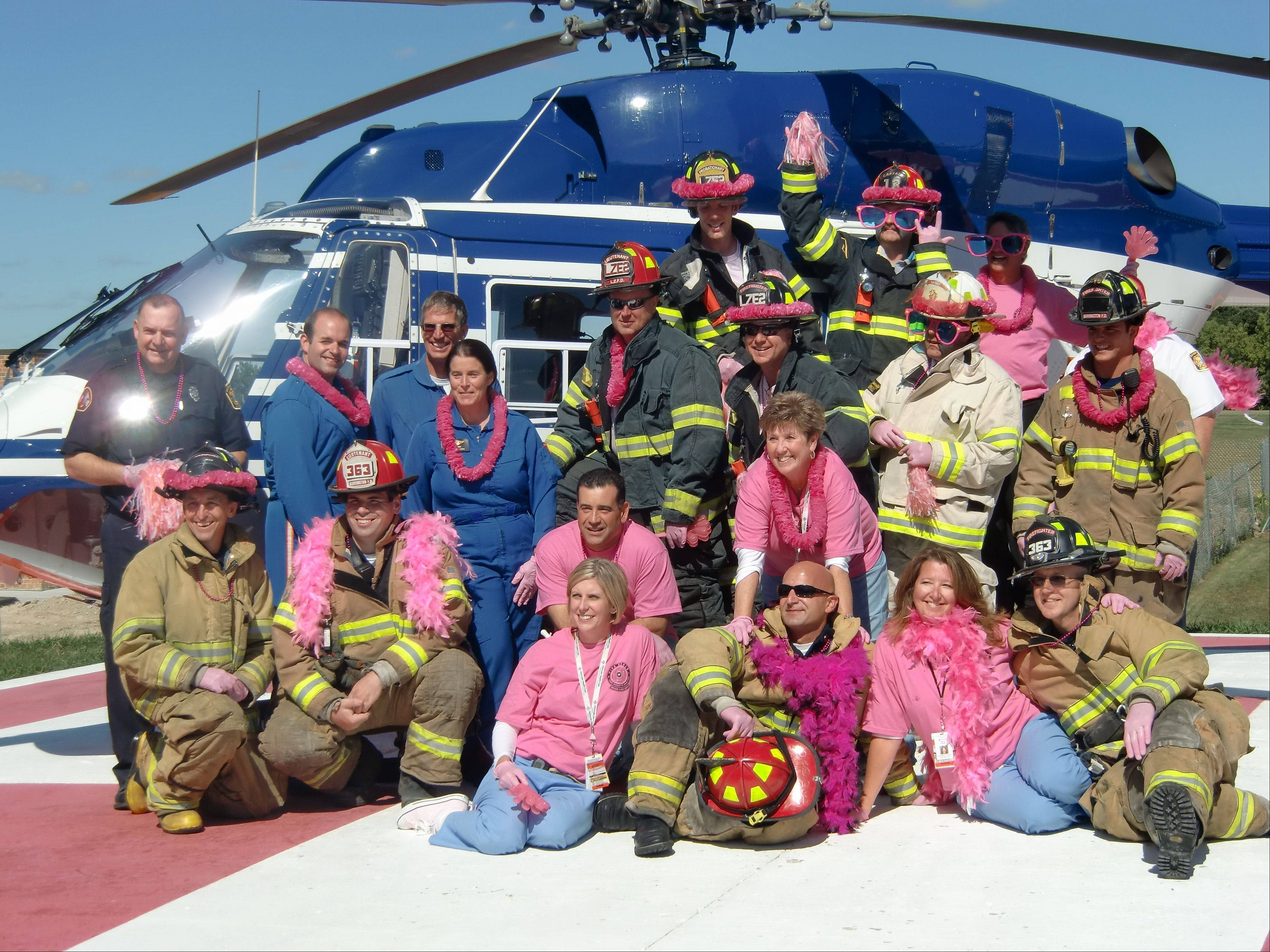 The Flight for Life helicopter from McHenry serves as the backdrop for firefighters and Good Shepherd Emergency Department staff participating in the video production.