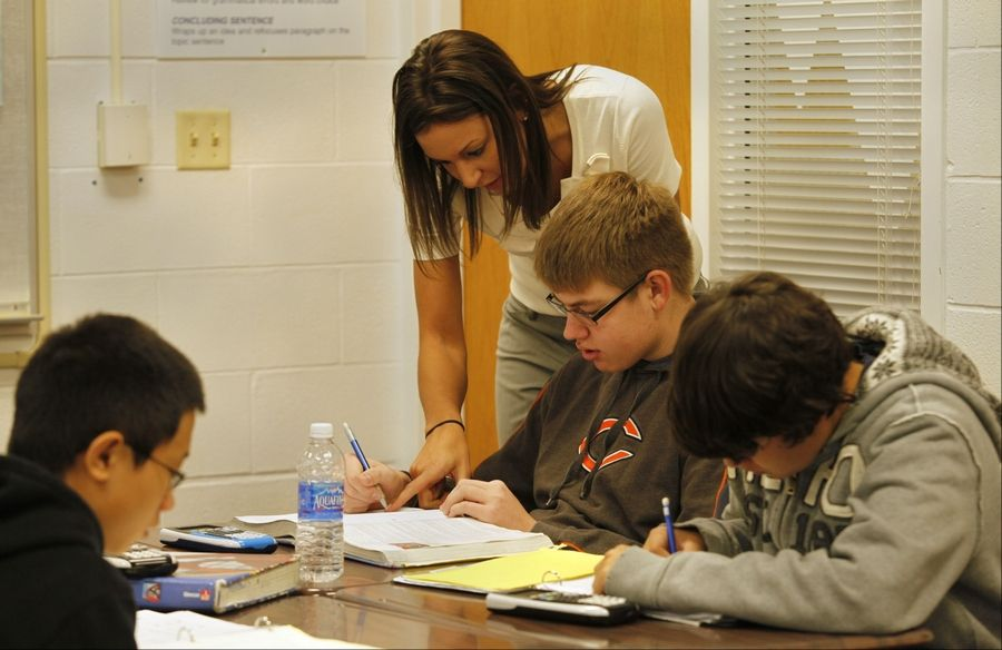 Honors Algebra II teacher Kristin Tuma works with junior Bryan Jones at Jacobs High School, where students made significant gains on statewide math testing.