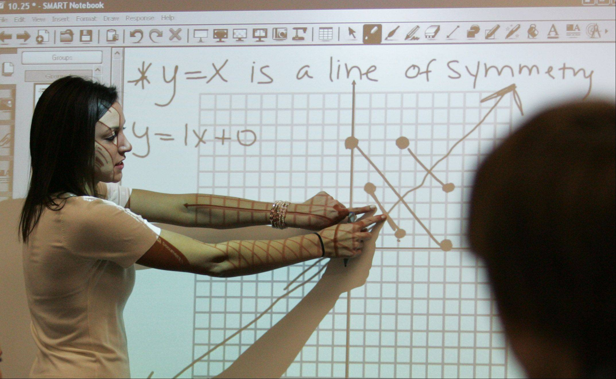 "Honors Algebra II teacher Kristin Tuma graphs some problems on the ""SMART Board"" at Jacobs High School in Algonquin."