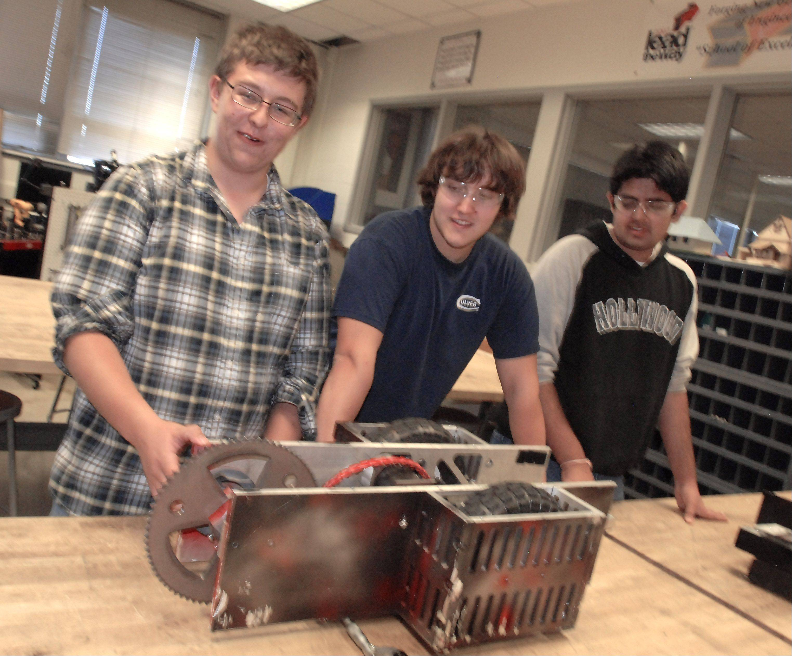 From left, sophomore Nick Crumbaugh and seniors Dan Shriber and Yogesh Kanal demonstrate part of the robot they built in Wheeling High School's manufacturing lab for an area BattleBots competition.