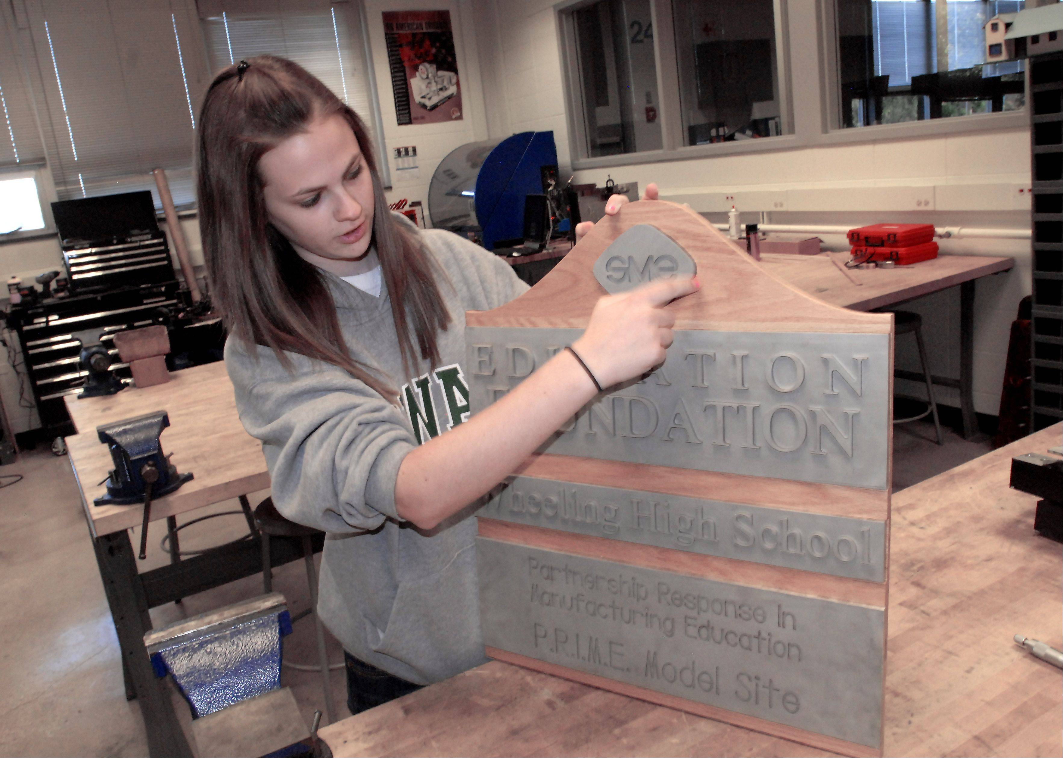 Wheeling High School sophomore Stacey Wojtkiewicz describes intricacies in her metalwork for a Society of Manufacturing Engineers Educational Foundation sign made in the school's manufacturing lab.