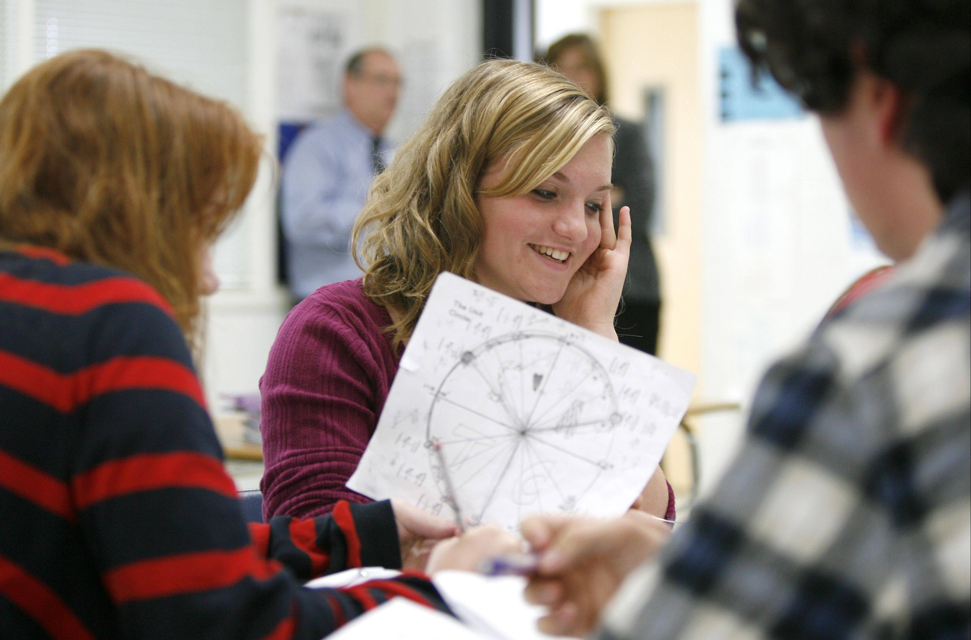 Christine Young, center, solves a problem during Mike Coit's honors pre-calculus class at Lisle Senior High School, where average composite ACT scores jumped from 22.0 in 2010 to 23.1 this year.
