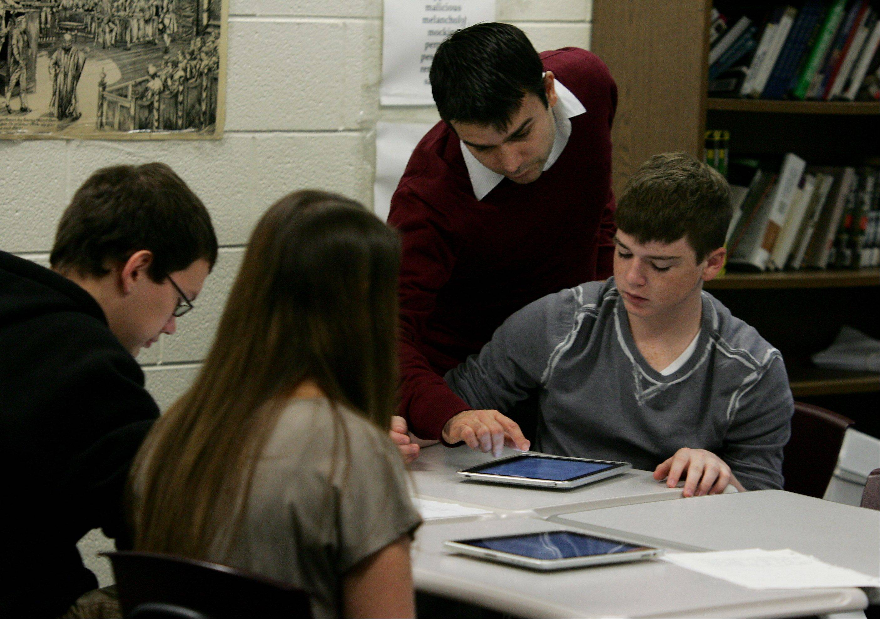 Sophomore English teacher Joseph Geocaris works with students using iPads on assignments at Stevenson High School in Lincolnshire.