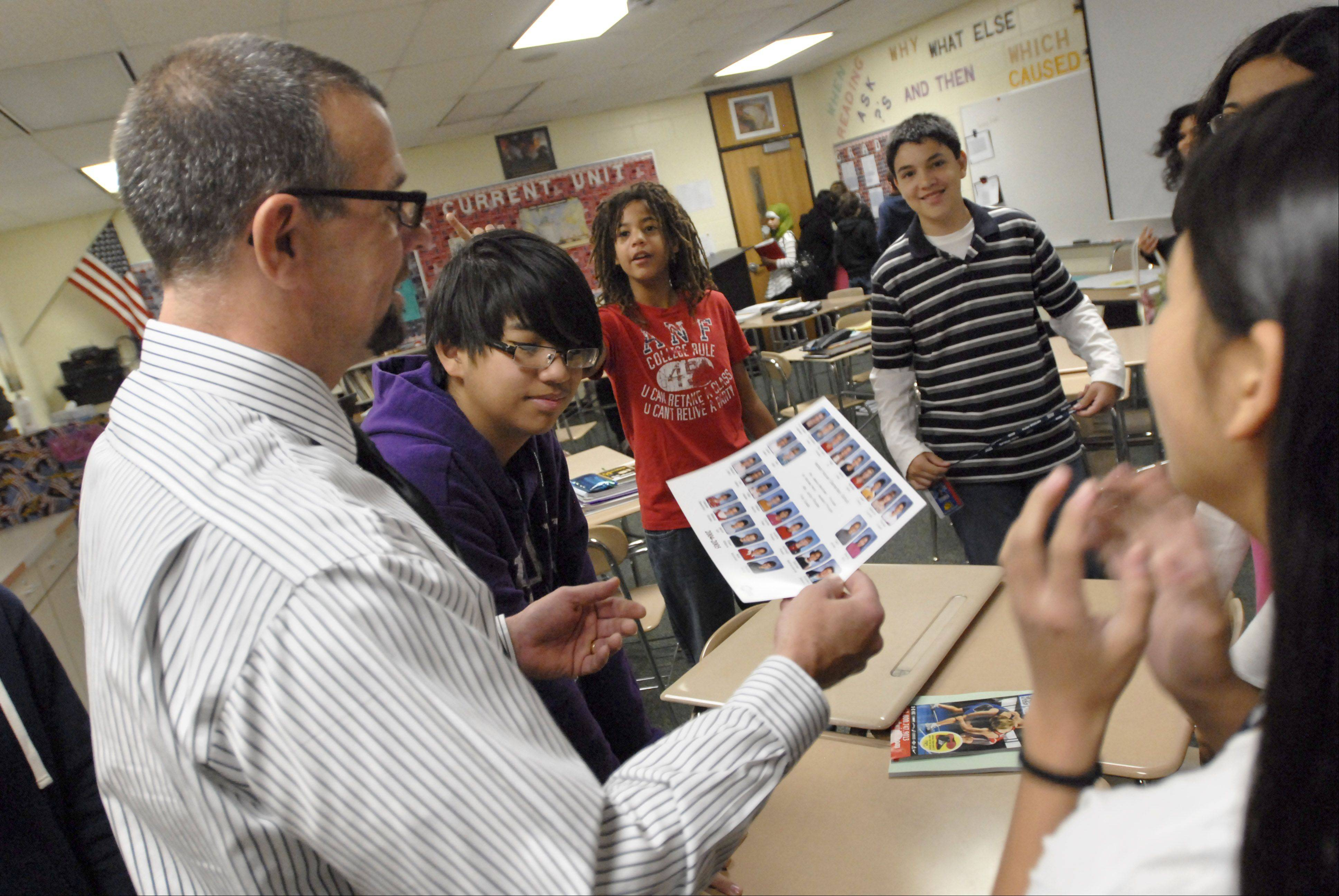 Teacher Mark Shydlowski looks at an old class photo with students in their homeroom at Helen Keller School in Schaumburg. A new 20-minute homeroom period helps teachers identify students who have problems with tardiness or behavior, which may affect test scores.