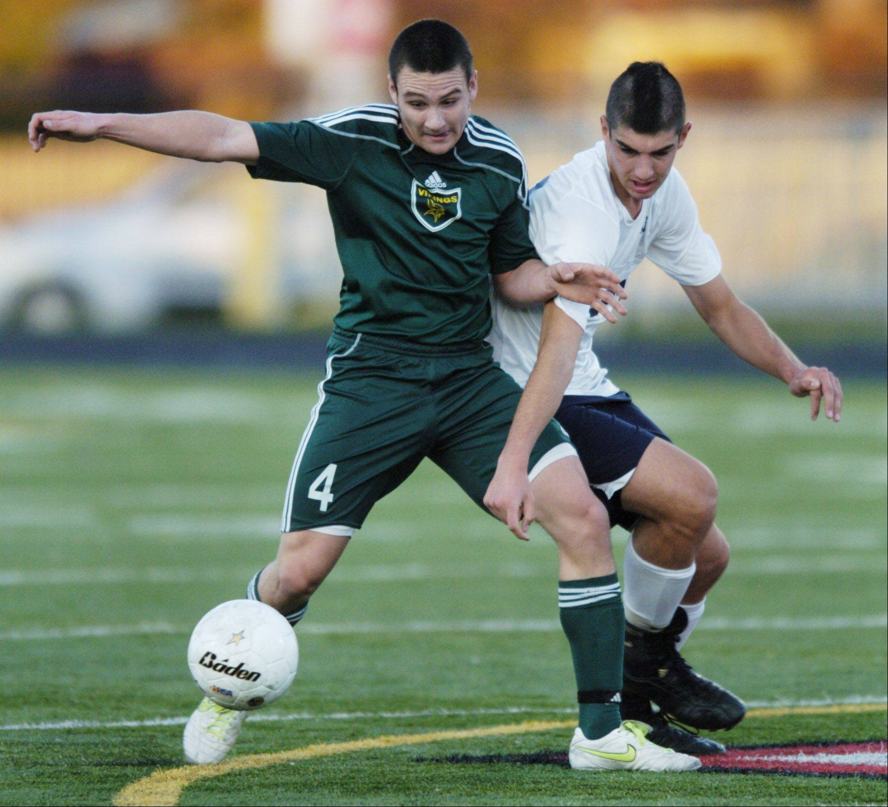 Fremd's Michael Eschbach, left, tries to hold off New Trier's Jeff Farina during Tuesday's boys soccer supersectional game at Maine South.