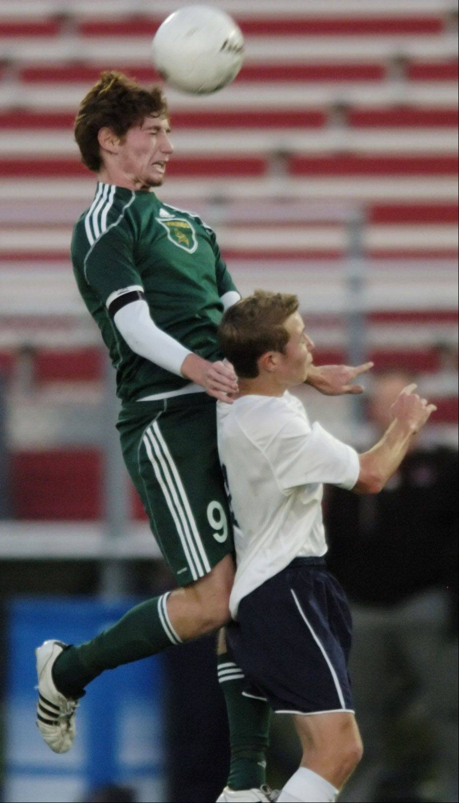 Fremd's Jeremy Kosacz, left, leaps for a header during boys soccer supersectional game against New Trier Tuesday.
