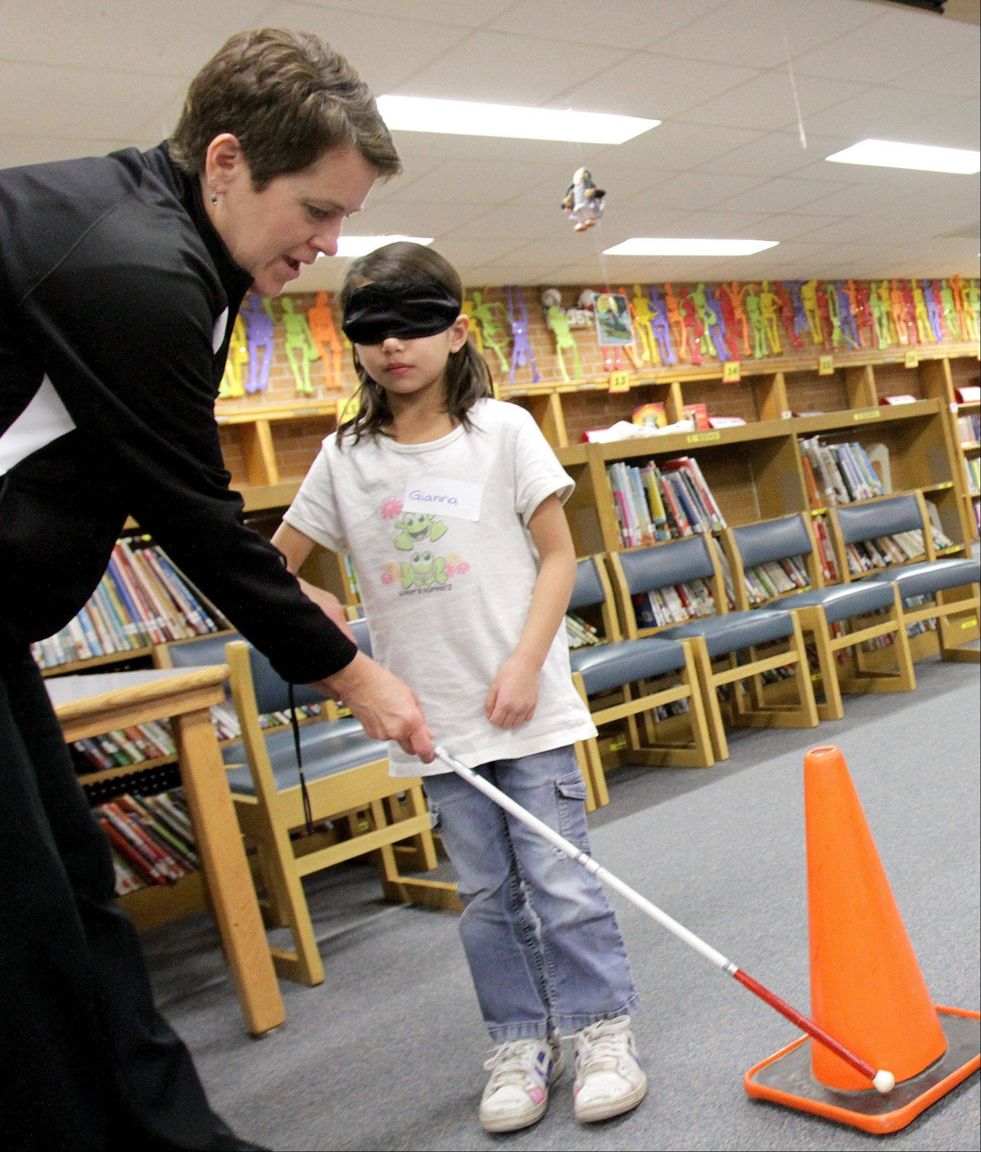 Lori Miller, left, manager of program development at Northeast DuPage Special Recreation Association, helps Gianna Pon use a cane for the blind on Wednesday at Benson Primary School in Itasca.