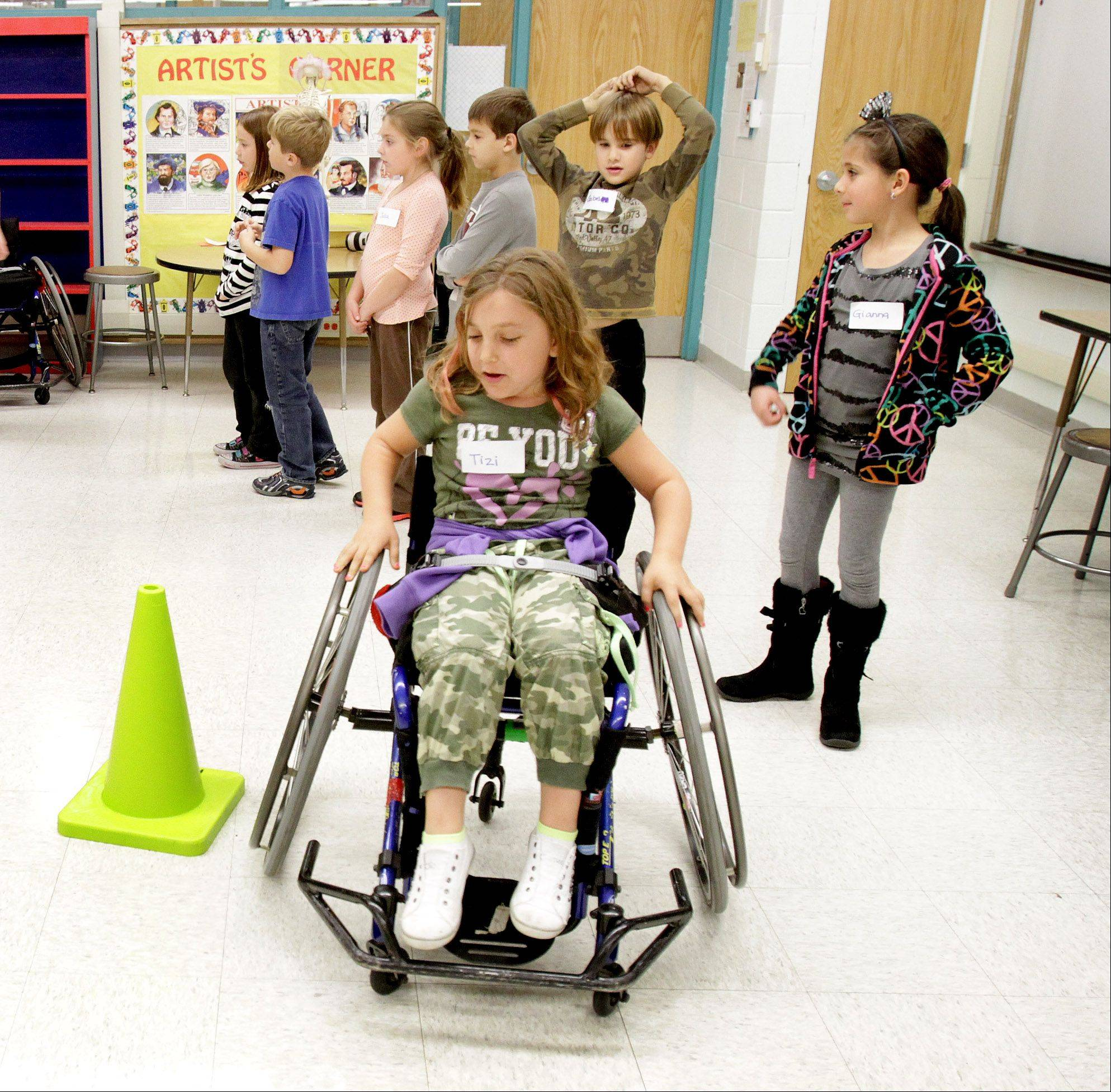 Tizi Lampignano uses a sports wheelchair as second-graders at Benson Primary School in Itasca participated in an ability awareness program.
