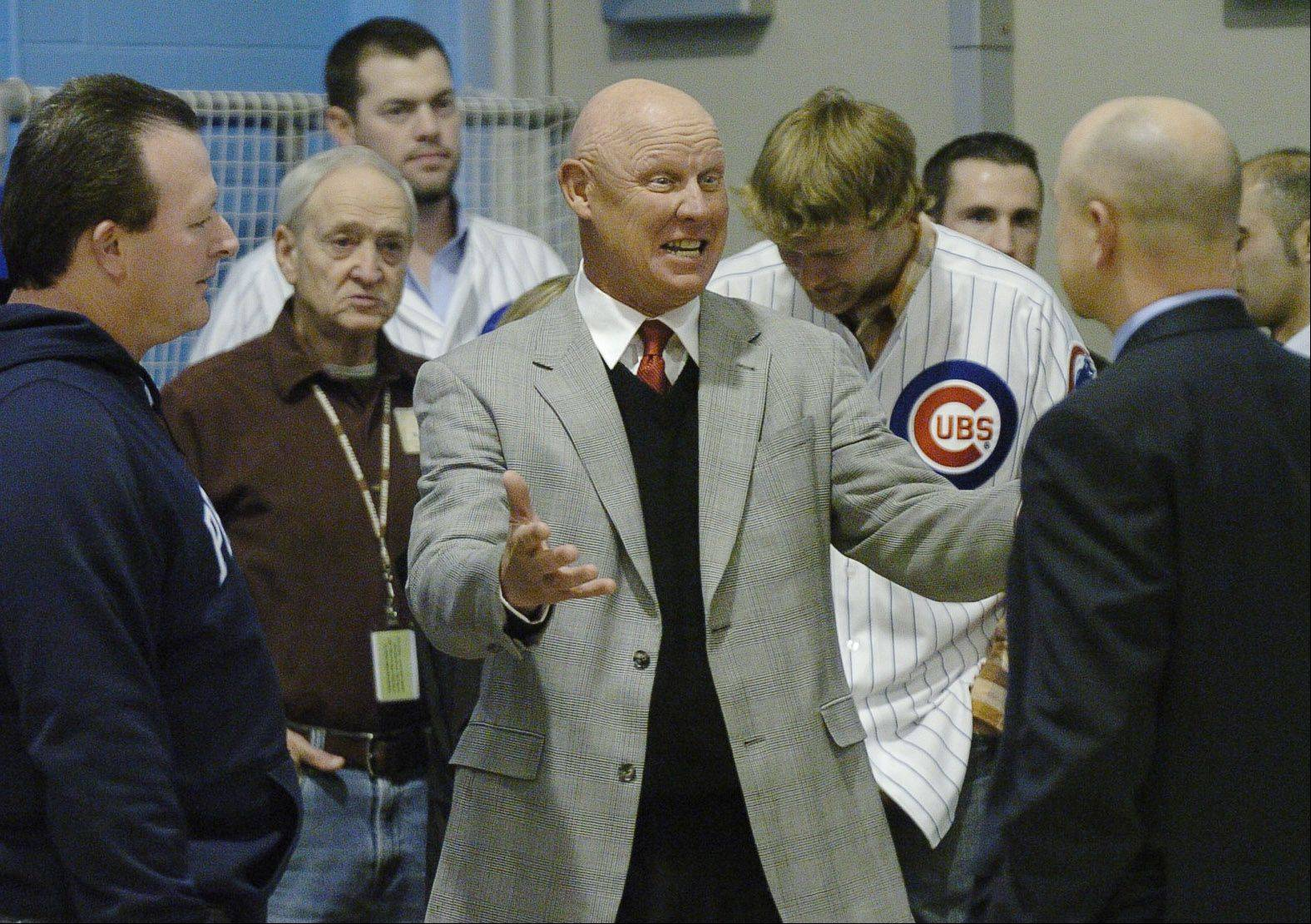 Cubs manager Mike Quade is greeted by principal Kurt Laakso, right, and baseball coach Ross Giusti, left, as he arrives for his visit to his Alma Mater, Prospect High.