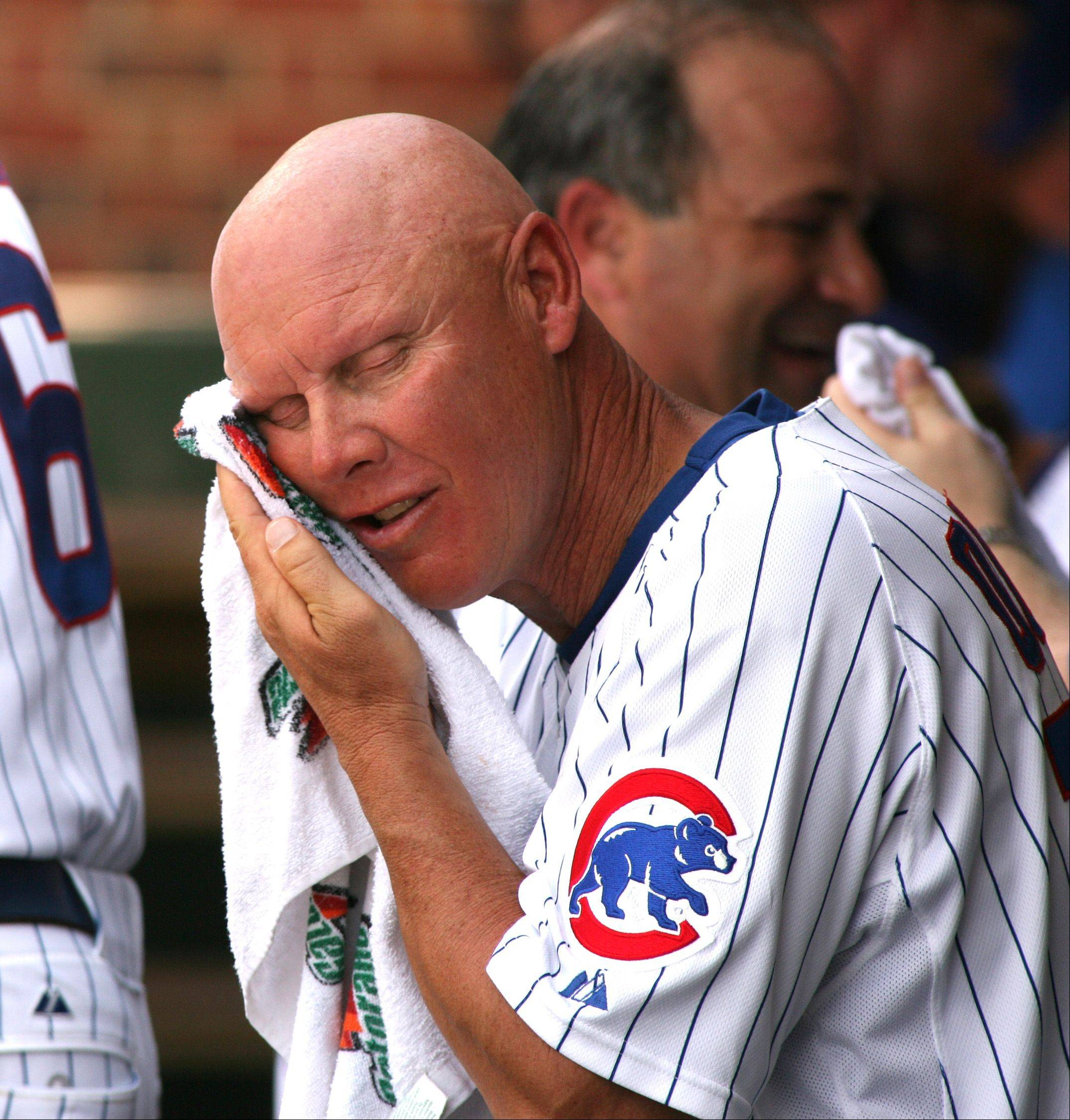 Chicago Cubs third base coach Mike Quade towels off some heat during a game against the Colorado Rockies.