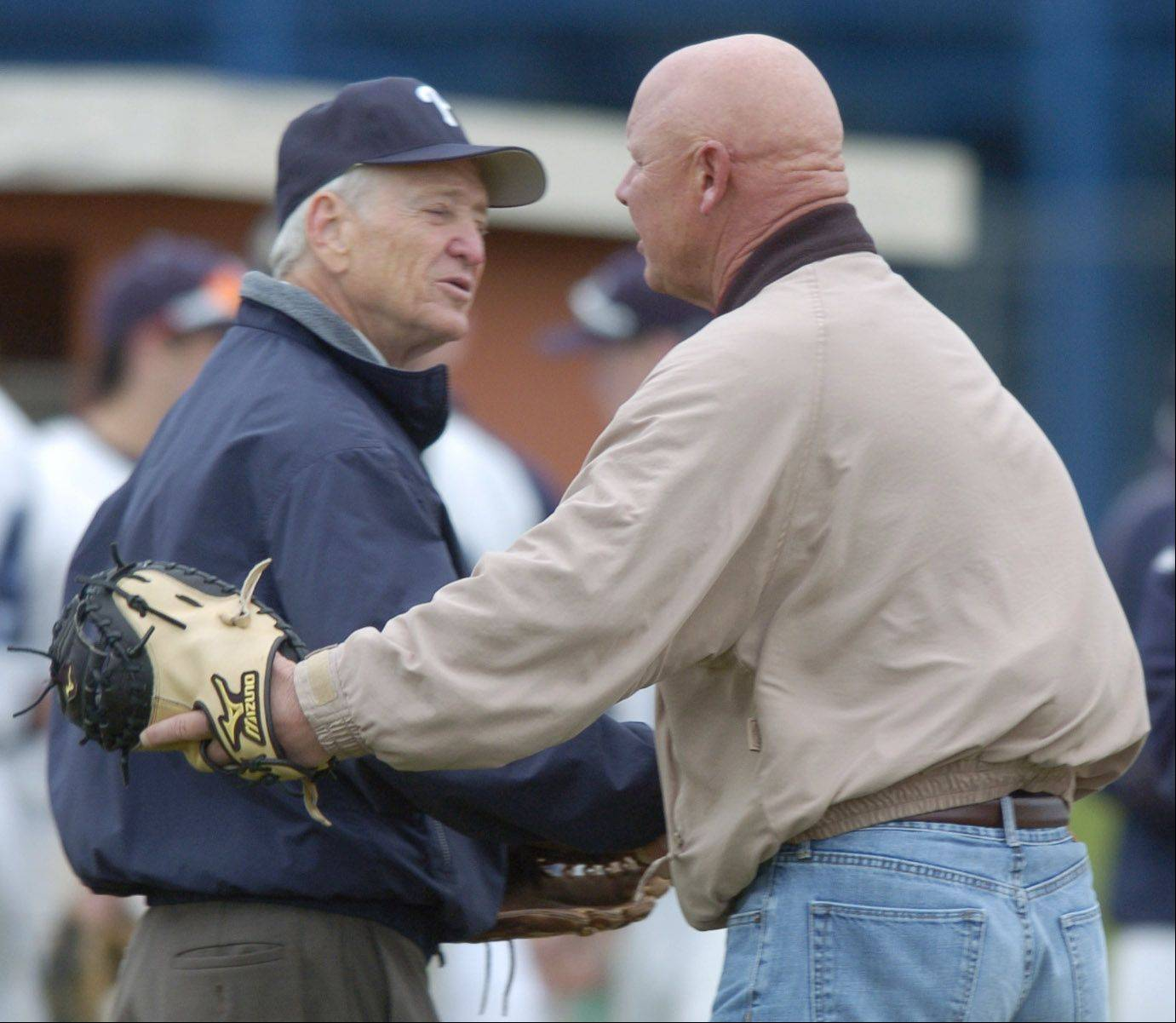 Retired Prospect High School baseball coach Larry Pohlman, left, is congratulated by Chicago Cubs manager and Prospect alumnus Mike Quade after Pohlman threw out the cermonial first pitch before a game against Hersey. The Prospect varsity baseball field was dedicated to Pohlman during a pre-game ceremony.