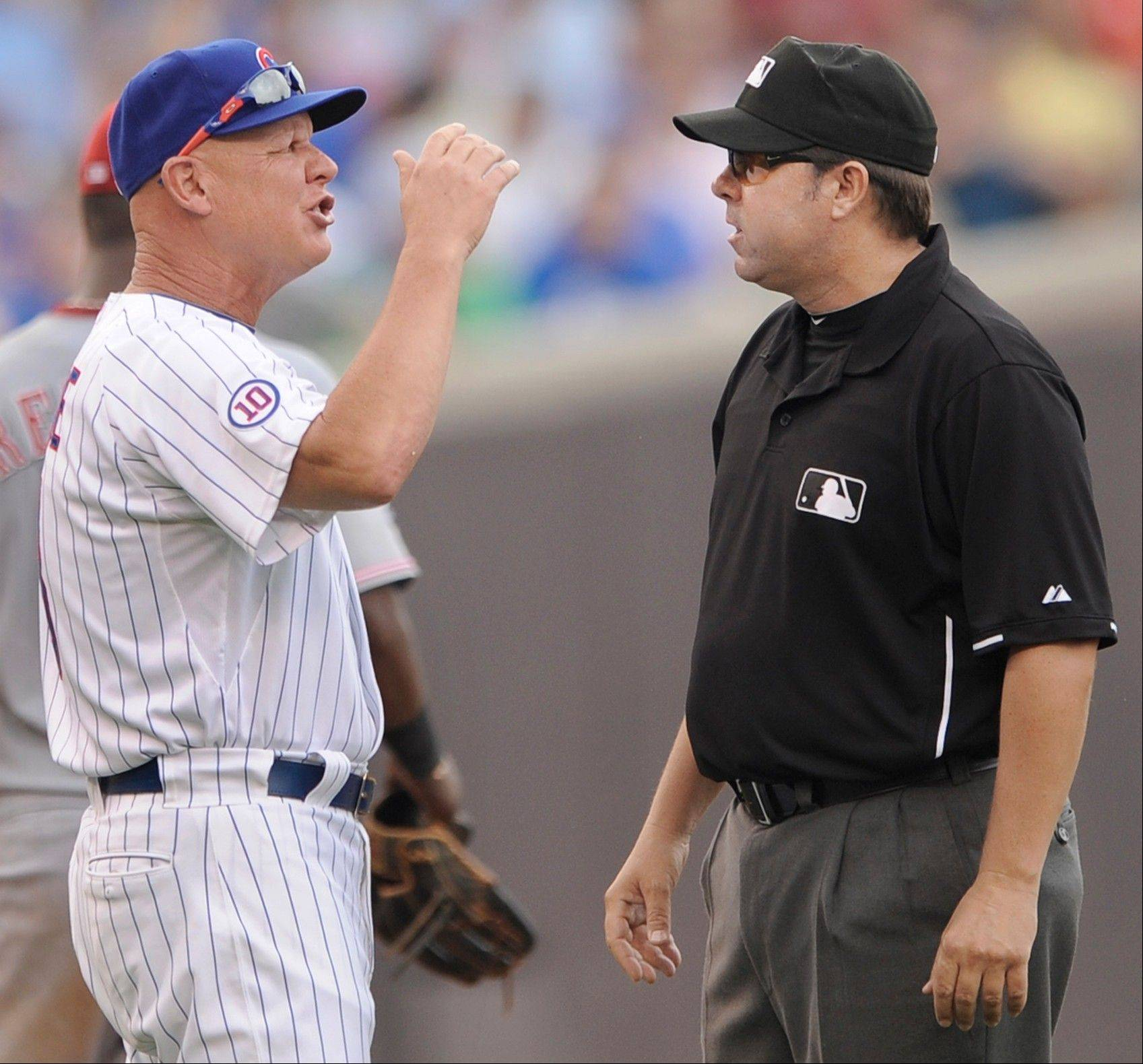 Chicago Cubs manager Mike Quade left, argues with second base umpire Doug Eddings during the fourth inning of a baseball game against the Cincinnati Reds in Chicago, Saturday, Aug. 6, 2011. Chicago won 11-4.