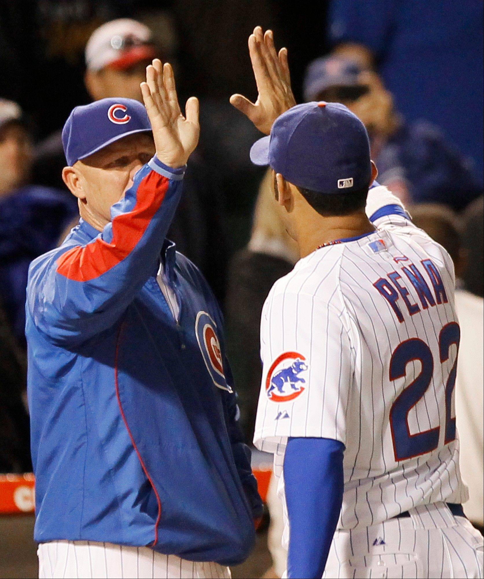 Chicago Cubs manager Mike Quade, left, celebrates with first baseman Carlos Pena after a baseball game and Cubs' 6-3 win over the Cincinnati Reds, Wednesday, Sept. 7, 2011 in Chicago.