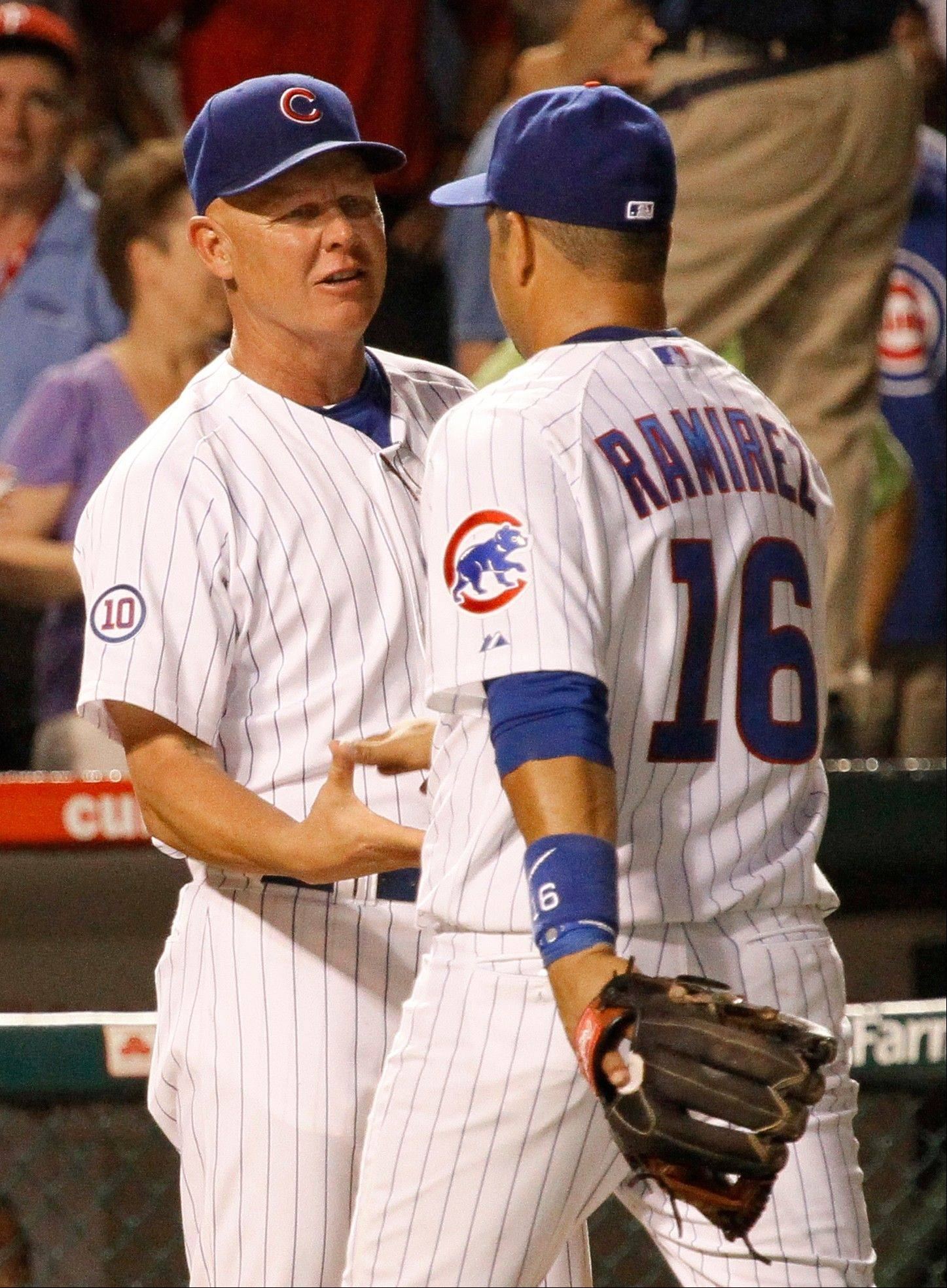 Chicago Cubs manager Mike Quade, left, celebrates with third baseman Aramis Ramirez their 6-1 win over the Philadelphia Phillies after a baseball game Monday, July 18, 2011 in Chicago.