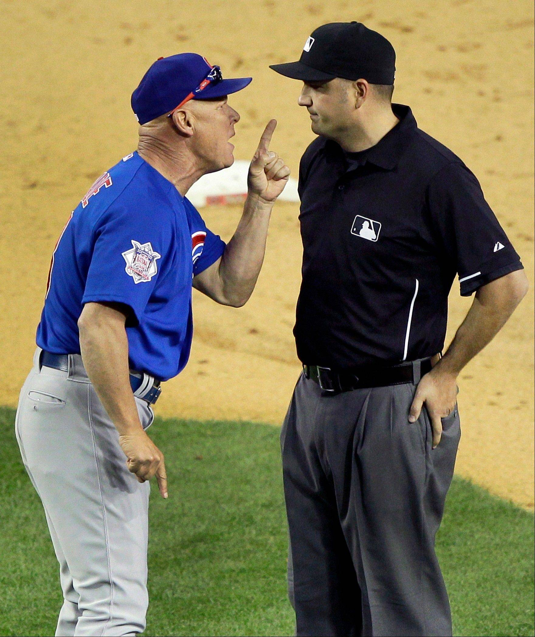 Chicago Cubs manager Mike Quade argues with umpire Dan Bellino after being ejected during the ninth inning of a baseball game against the Arizona Diamondbacks Saturday, April 30, 2011, in Phoenix.