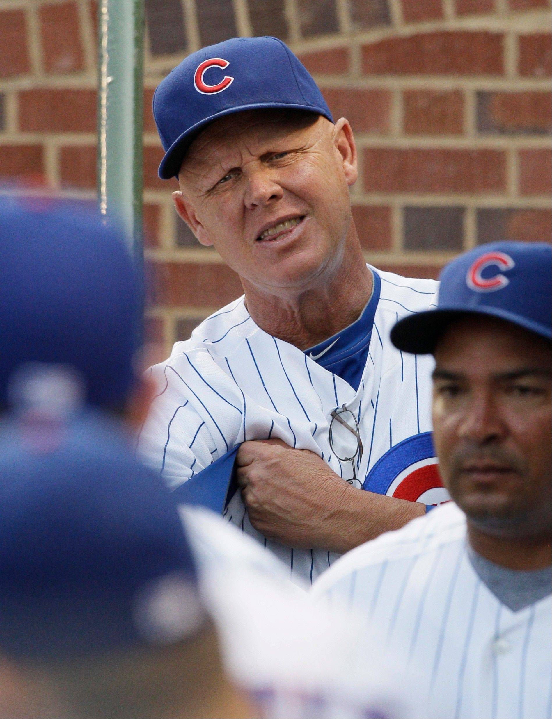Chicago Cubs manager Mike Quade looks to his team in the dugout before a baseball game against the Florida Marlins, Thursday, July 14, 2011, in Chicago.