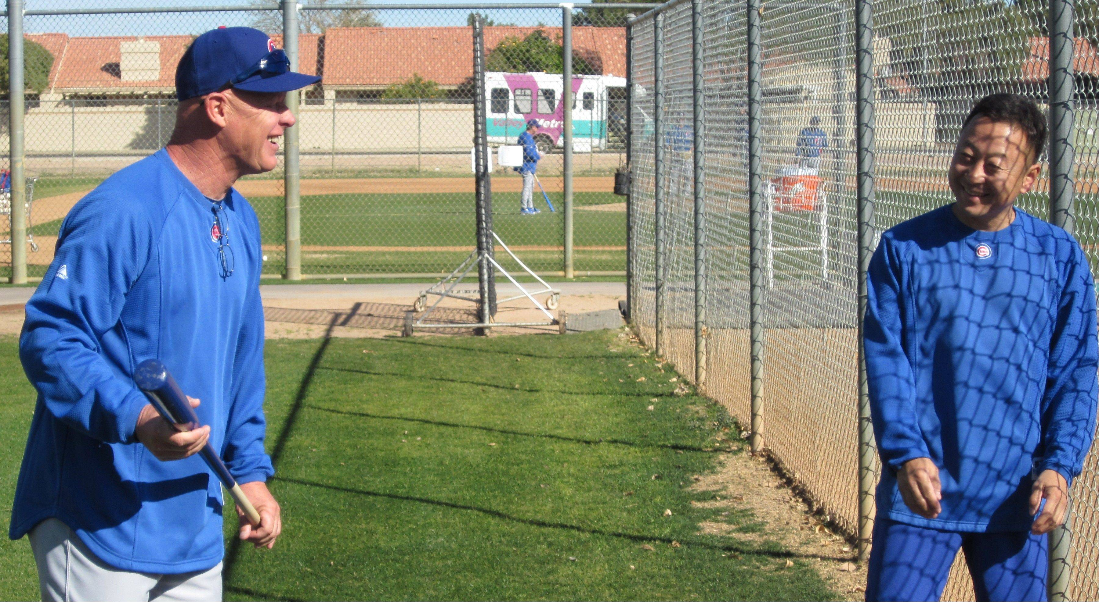 Cubs manager Mike Quade shares a laugh with assistant trainer Yoshi Nakazawa during workouts at Cubs camp in Mesa, Ariz.