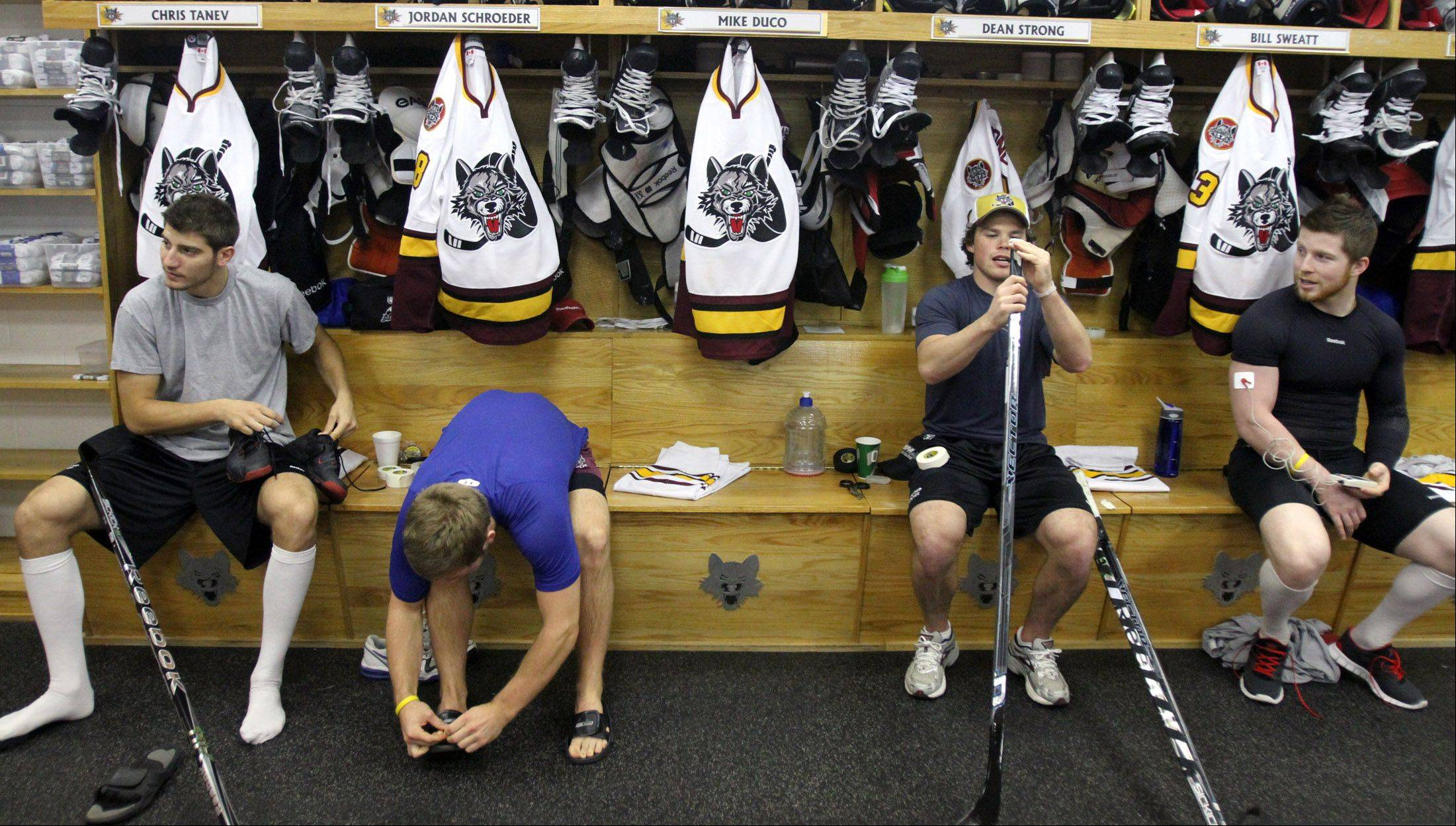 Chicago Wolves players Chris Tanev, center Jordan Schroeder, forward Dean Strong, and left wing Mike Duco prepare for their matchup with the Rockford IceHogs in the team's locker room at Allstate Arena.