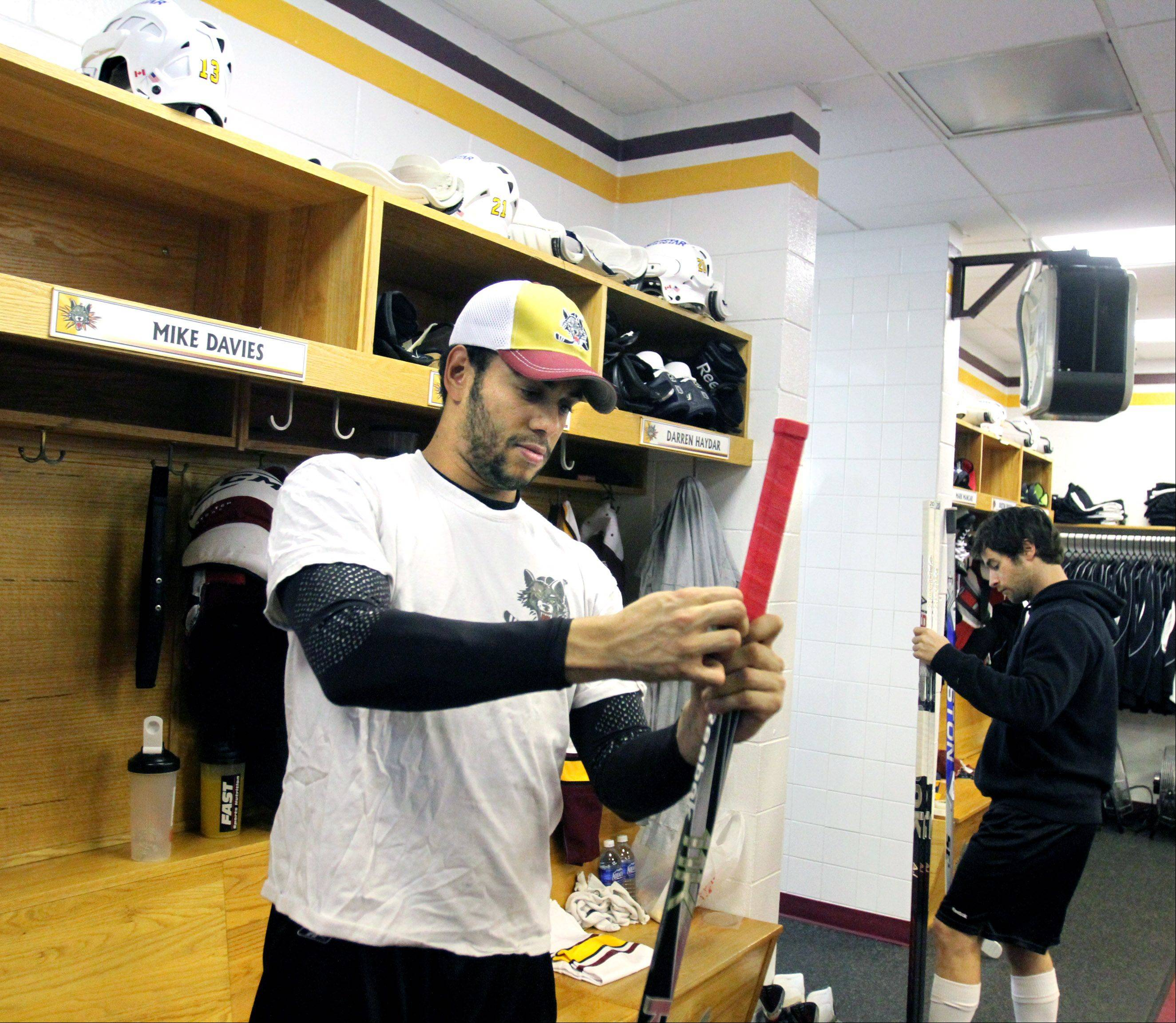 Chicago Wolves forward Michael Davies tapes the grip on his stick in the locker room before a game.