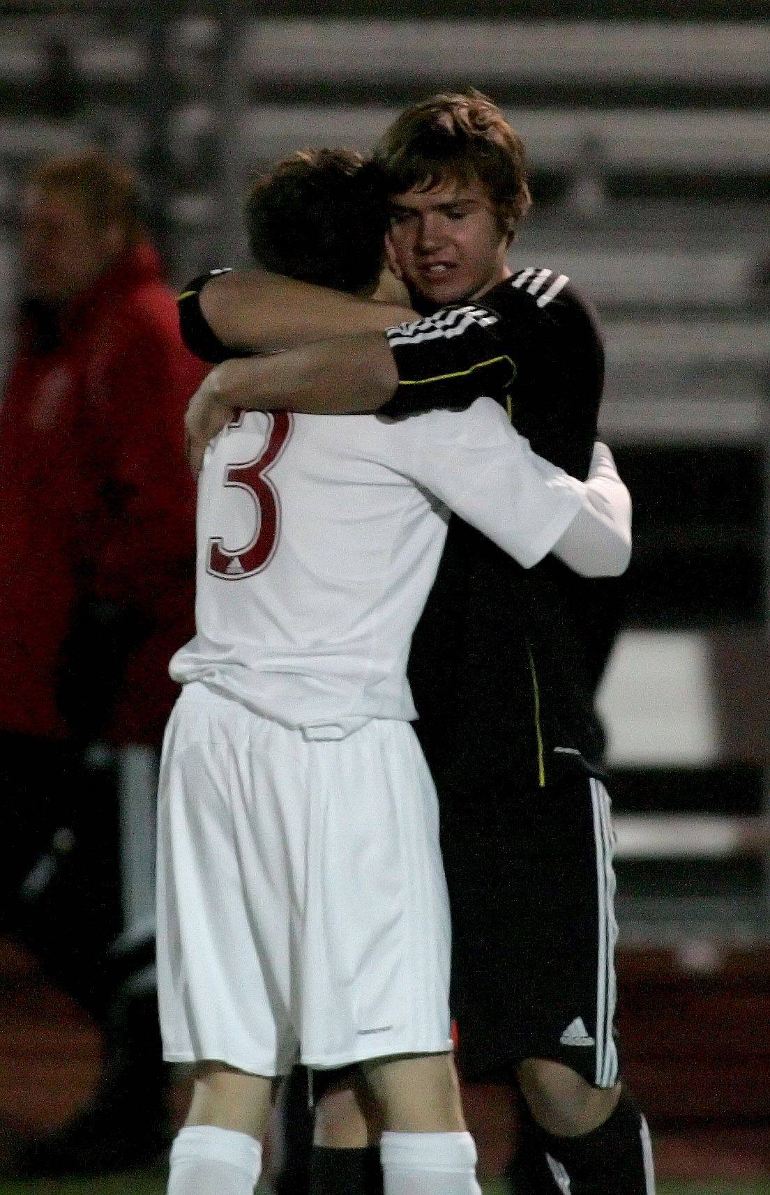 Jay Tegge hugs goalkeeper Mike Pavliga of Naperville Central after their 1-0 loss in overtime to Morton in the Class 3A state soccer championship game Saturday at Lincoln-Way North High School in Frankfort.