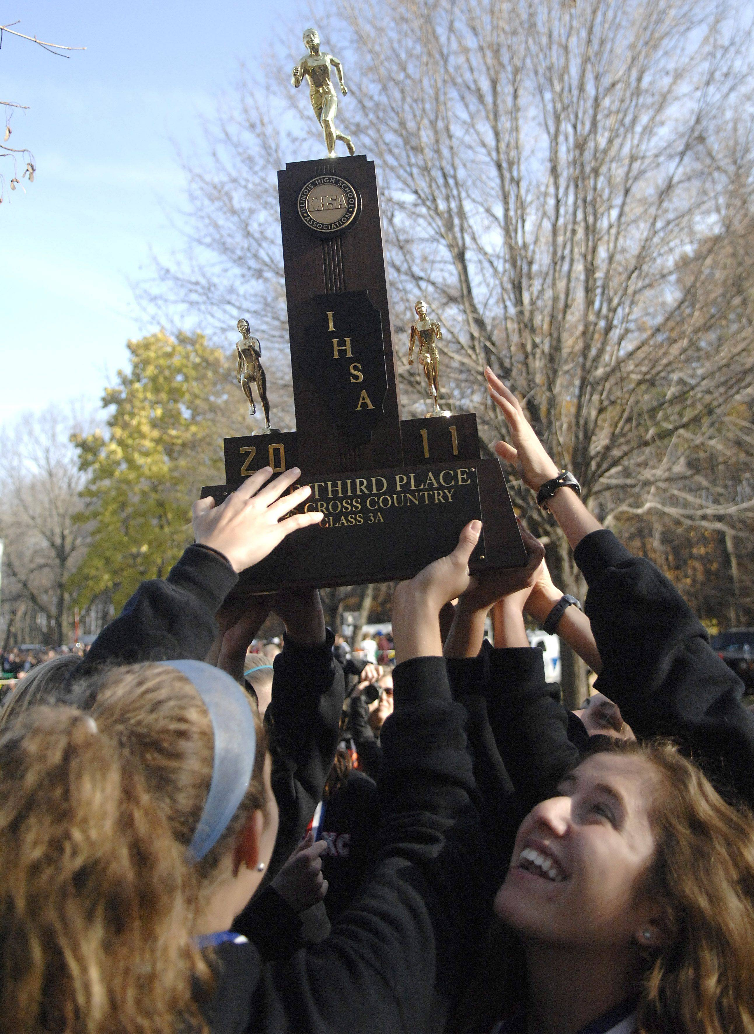 Naperville North girls hoist their third place 3A state trophy.