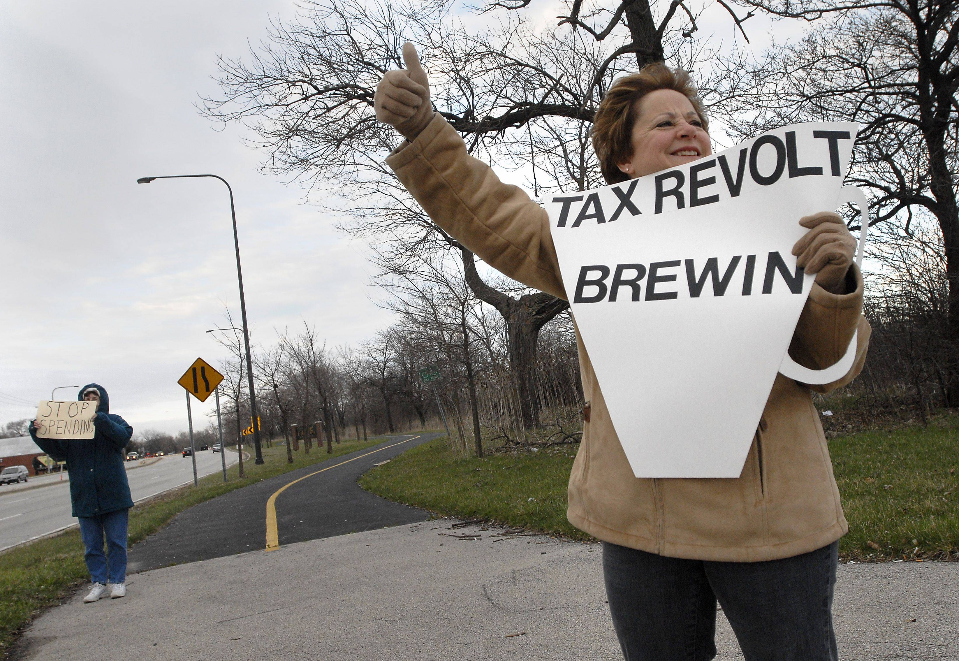 Bill Zars/bzars@dailyherald.com � Sue Gorden of Elk Gove Village give a thumbs up to a honking car during a Tea Bag anti-tax protest at Higgins and Arlington Heights Road in Elk Grove Village. Gorden said she was protesting because a 1000 page budget was passed in 48 hours and no one could have had time to read it properly. She said she is also opposed to government funding of abortion and stem cell research.