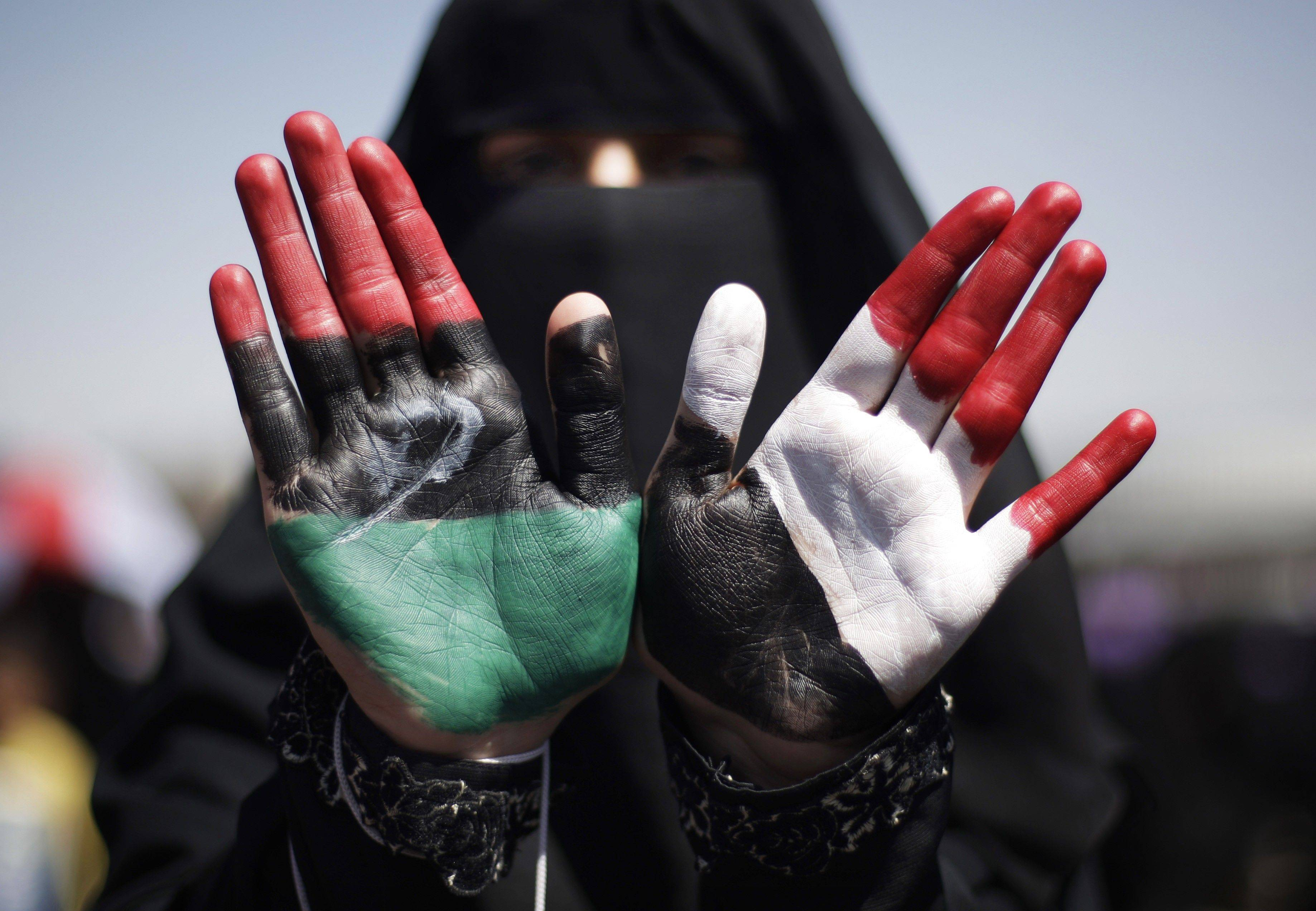A Yemeni female protestor with colors of the Libyan and Yemeni flags painted on her hands attends a demonstration demanding the resignation of Yemeni President Ali Abdullah Saleh in Sanaa, Yemen.